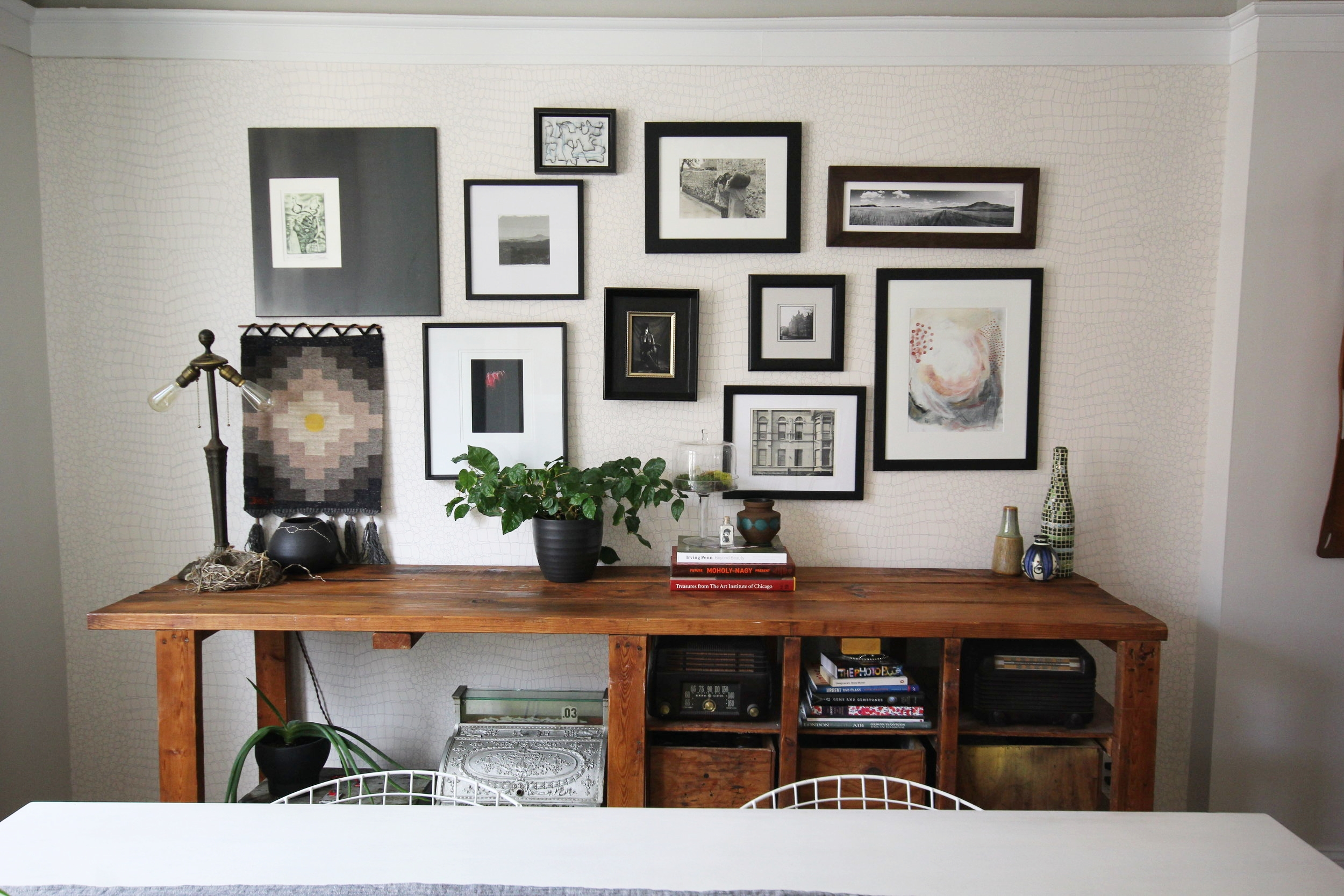 Wall with framed photos above a side board