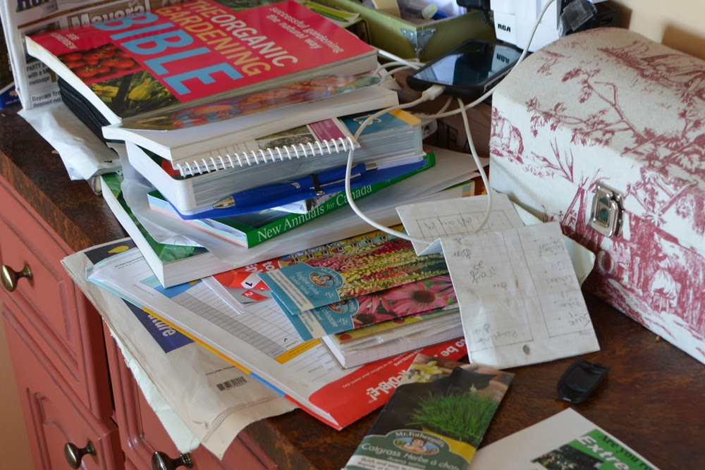 My oh-so-organized Spring Reading pile, decorated with seed packets and a crumpled garden plan on top.