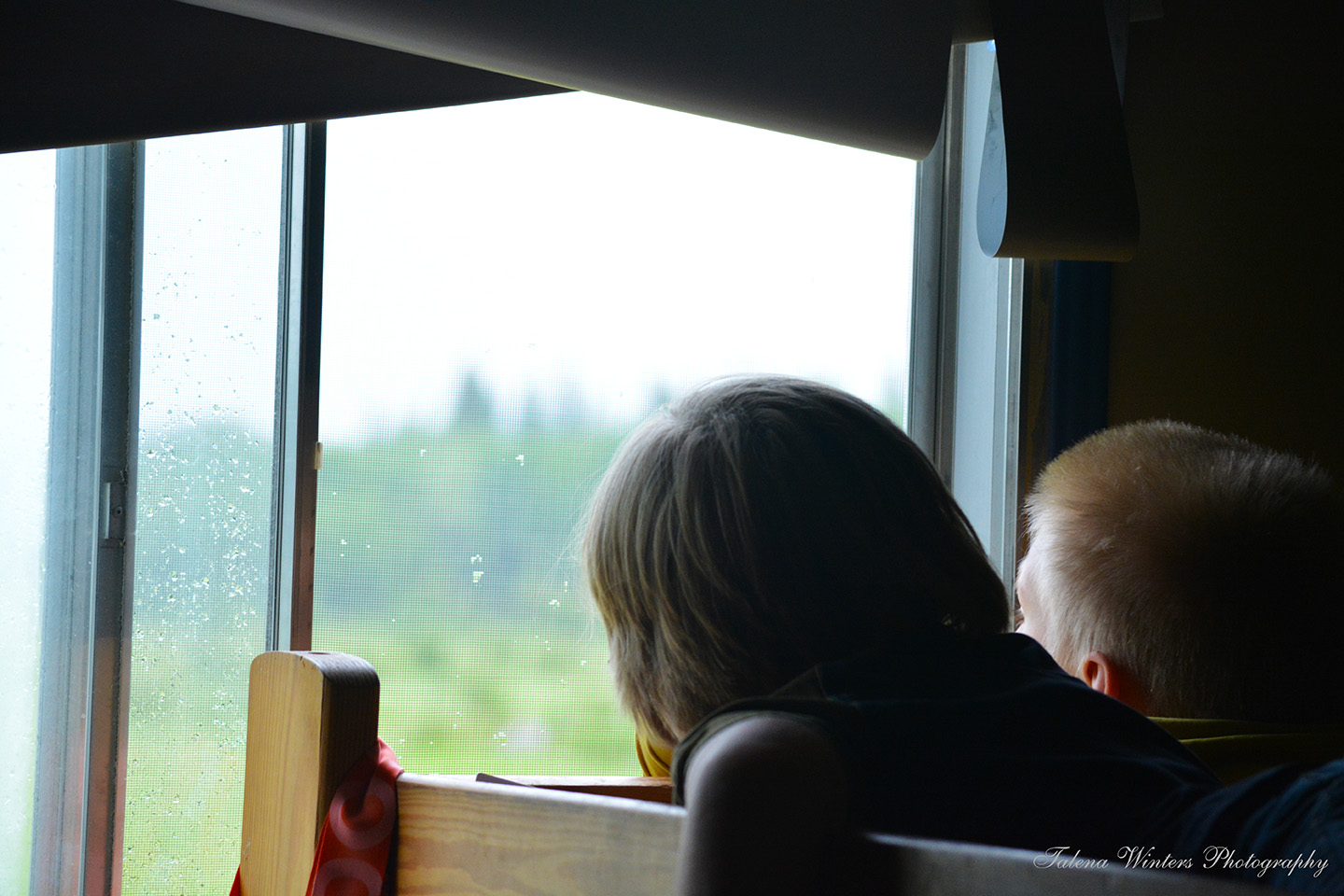 Jabin and Noah watch a lightning storm together on Noah's bunk. Lightning storms are rare here, so they were fascinated.