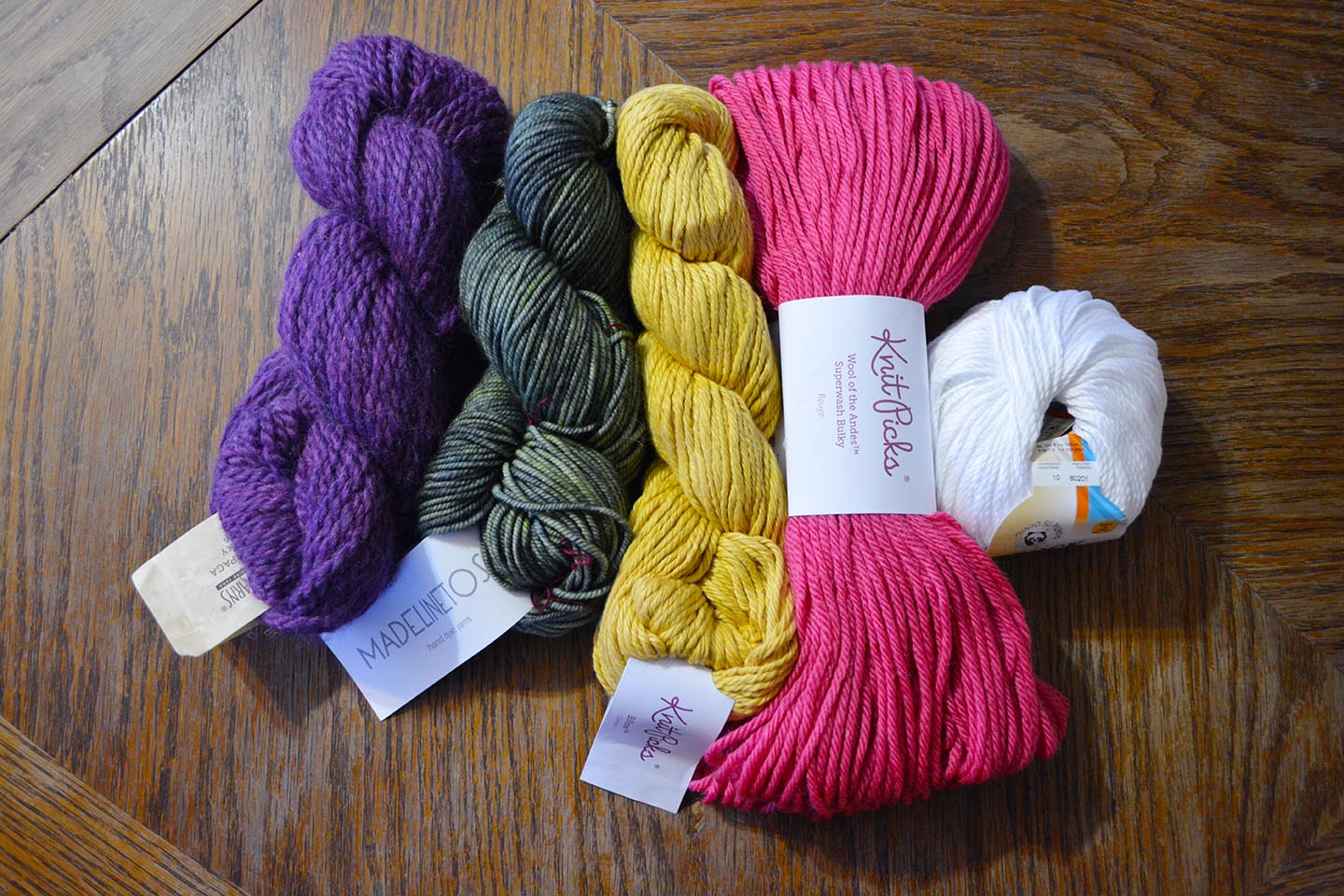 """These are all 100 g/3.5 oz skeins of """"Bulky"""" weight yarn (#5.) The yardages on each skein, from left to right, are: 108 yards, 165 yards, 120 yards, 137 yards, 132 yards."""