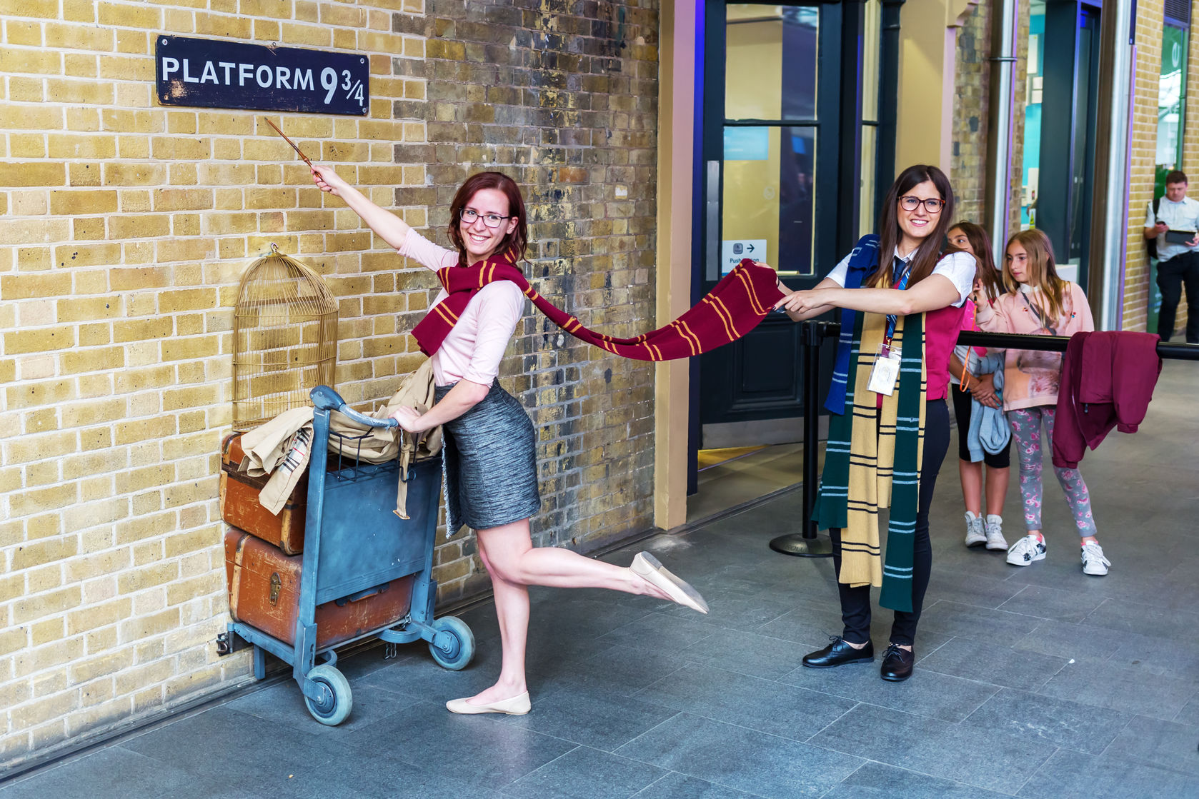 Potter fans pose at King's Cross Station's Platform 9 3/4. Photo copyright  madrabothair/123RF Stock Photos