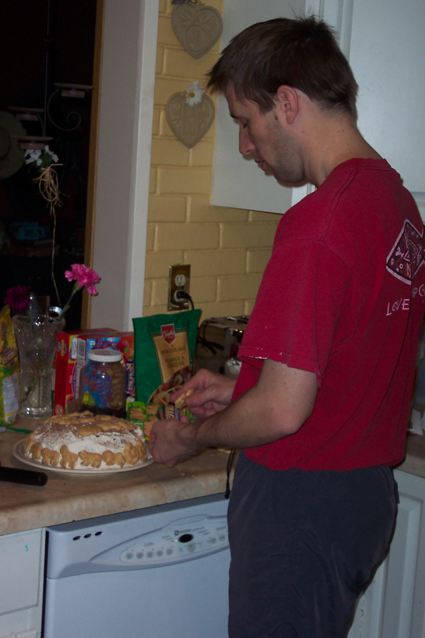 Jason decorating the cake with safari animal crackers.