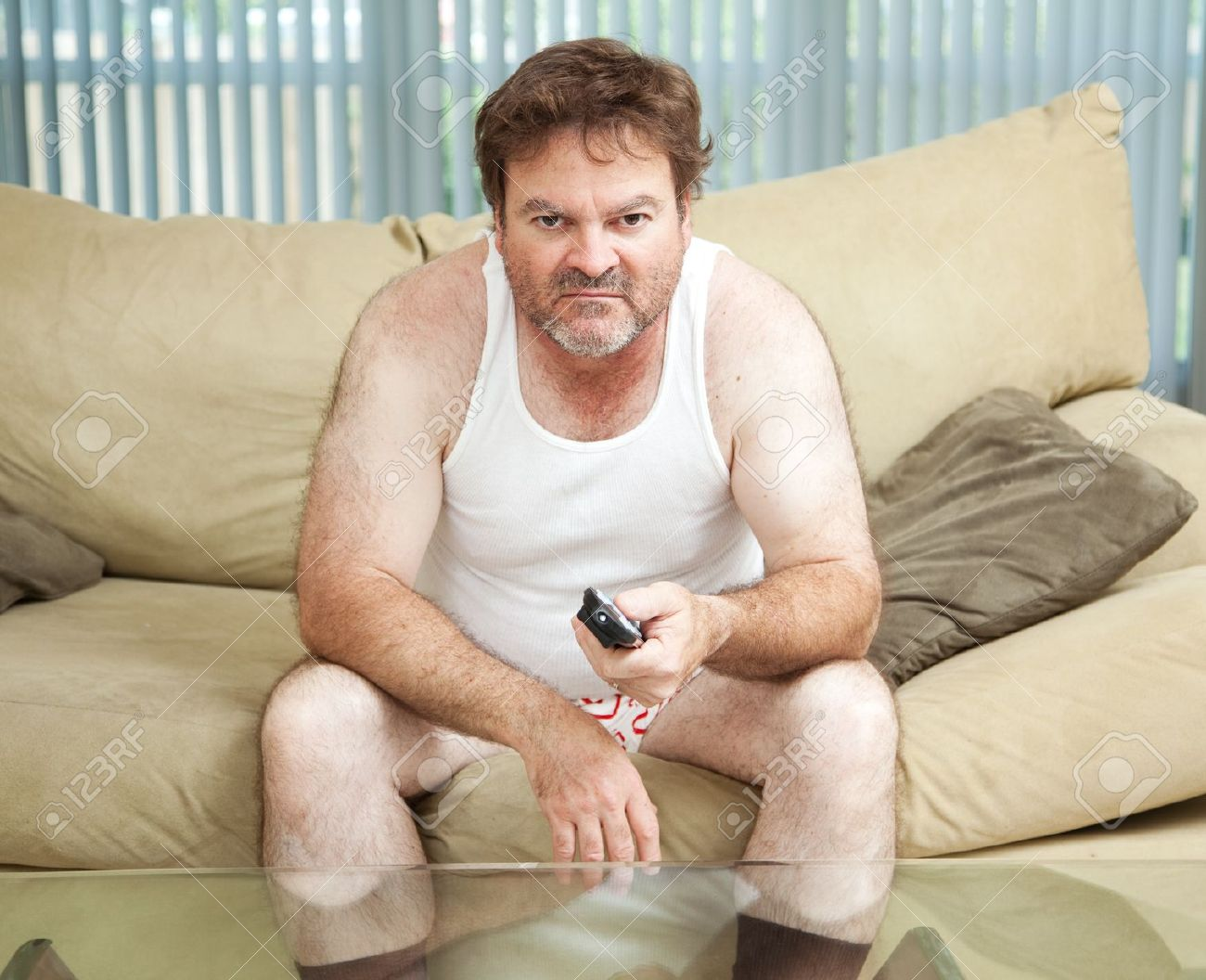 21788302-Unemployed-man-sitting-home-watching-TV-bored-and-discouraged--Stock-Photo.jpg