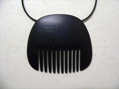 JAMES MCALLISTER (GUEST ARTIST)   Slotted Panel (Comb). stamped with text.Veil 4    2009   Black bakelite   80 x 70 mm