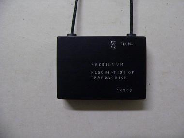 JAMES MCALLISTER (GUEST ARTIST)    Solid Black Tablet. stamped with text: Description of transactions...    2009   Black bakelite   45 x 65 mm