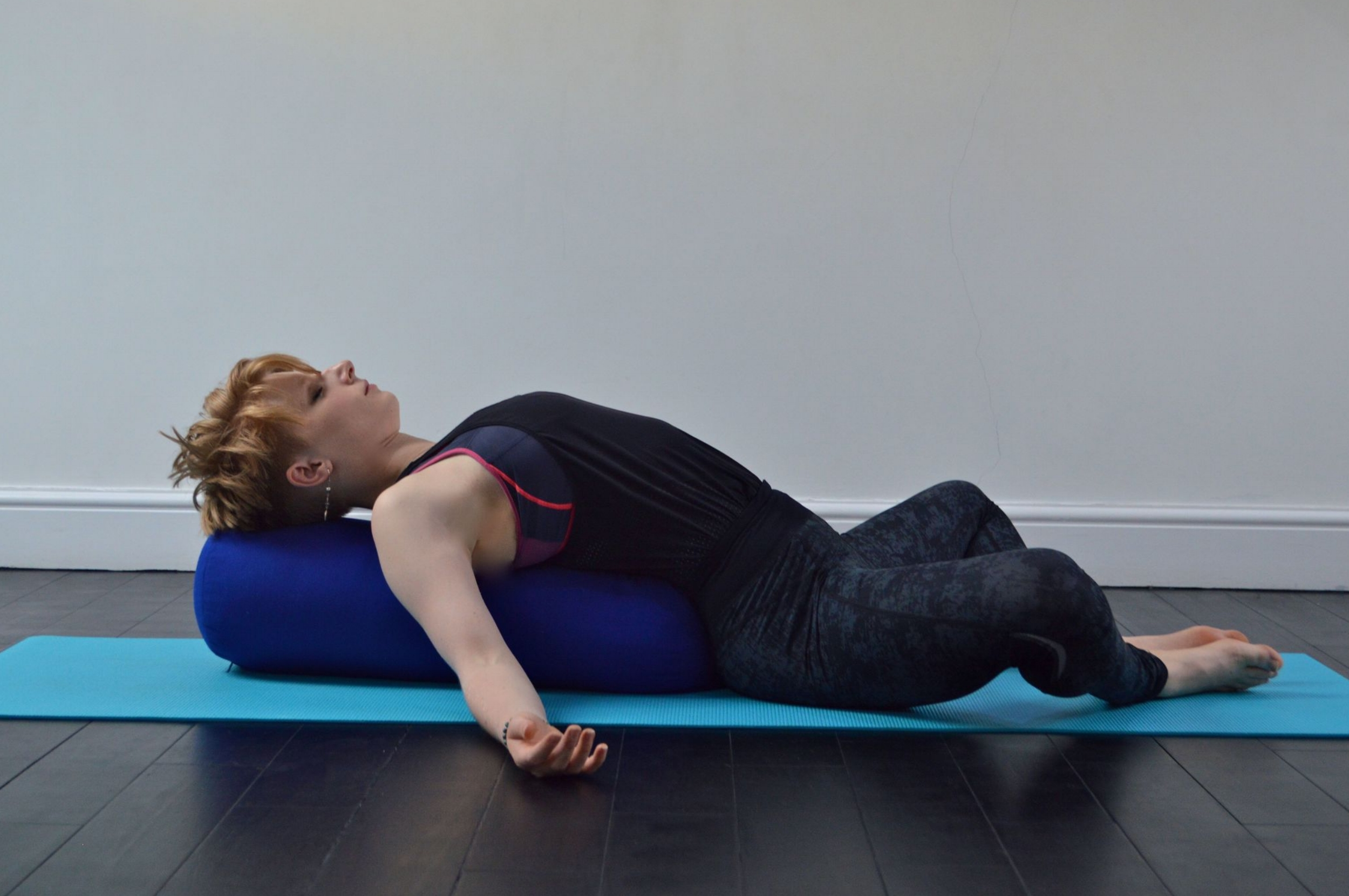 Rest the back of the body on a bolster or pillow, letting the chest open and the shoulders release away from the ears. The back of the neck is long, and your legs can be in any configuration that is comfortable. Close the eyes, soften the face, relax, and breathe.