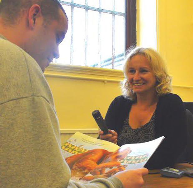 Sharon Berry helps an inmate record a story
