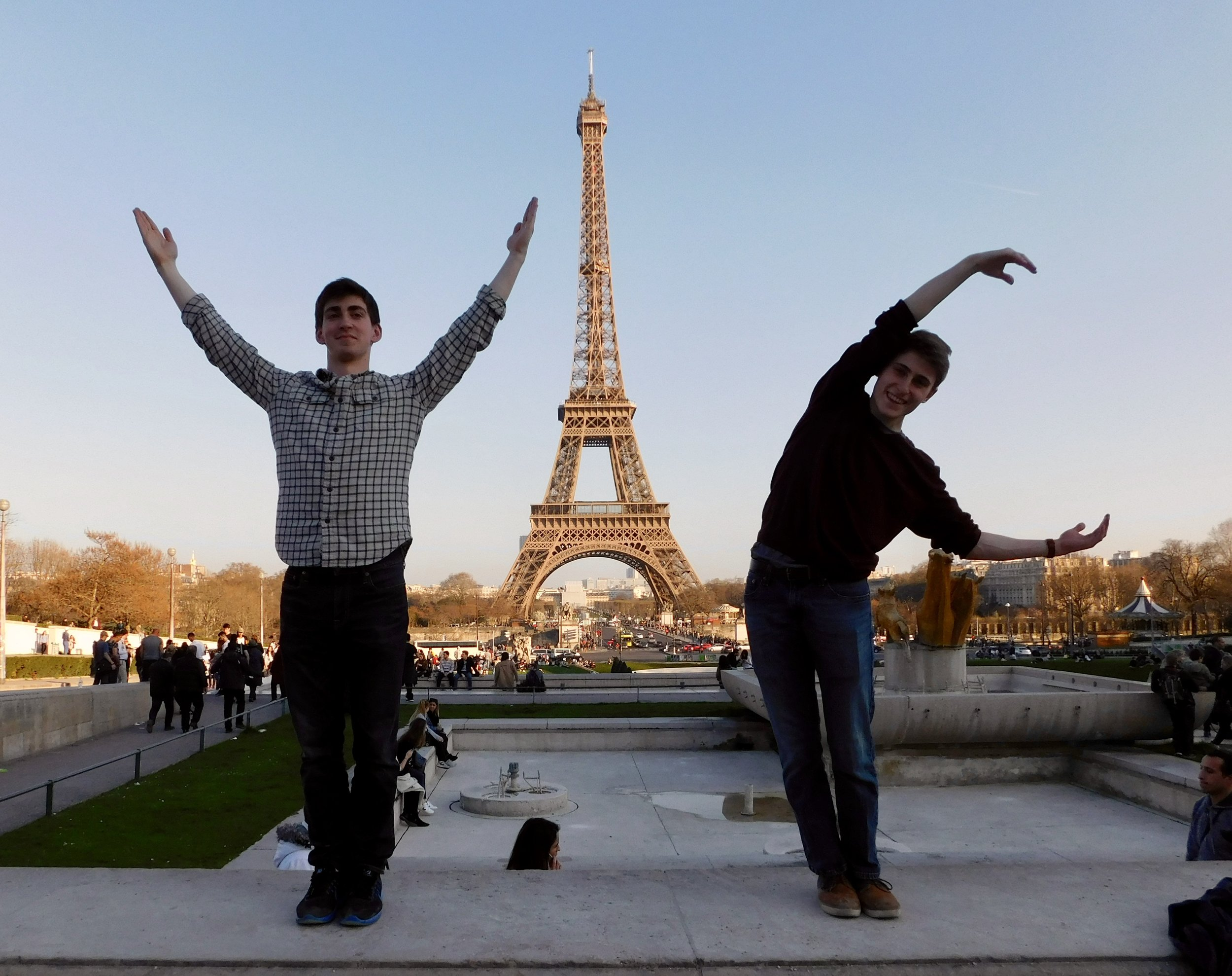 """Jacob and Hale framing a """"YAC"""" photo in front of the Eiffel Tower"""