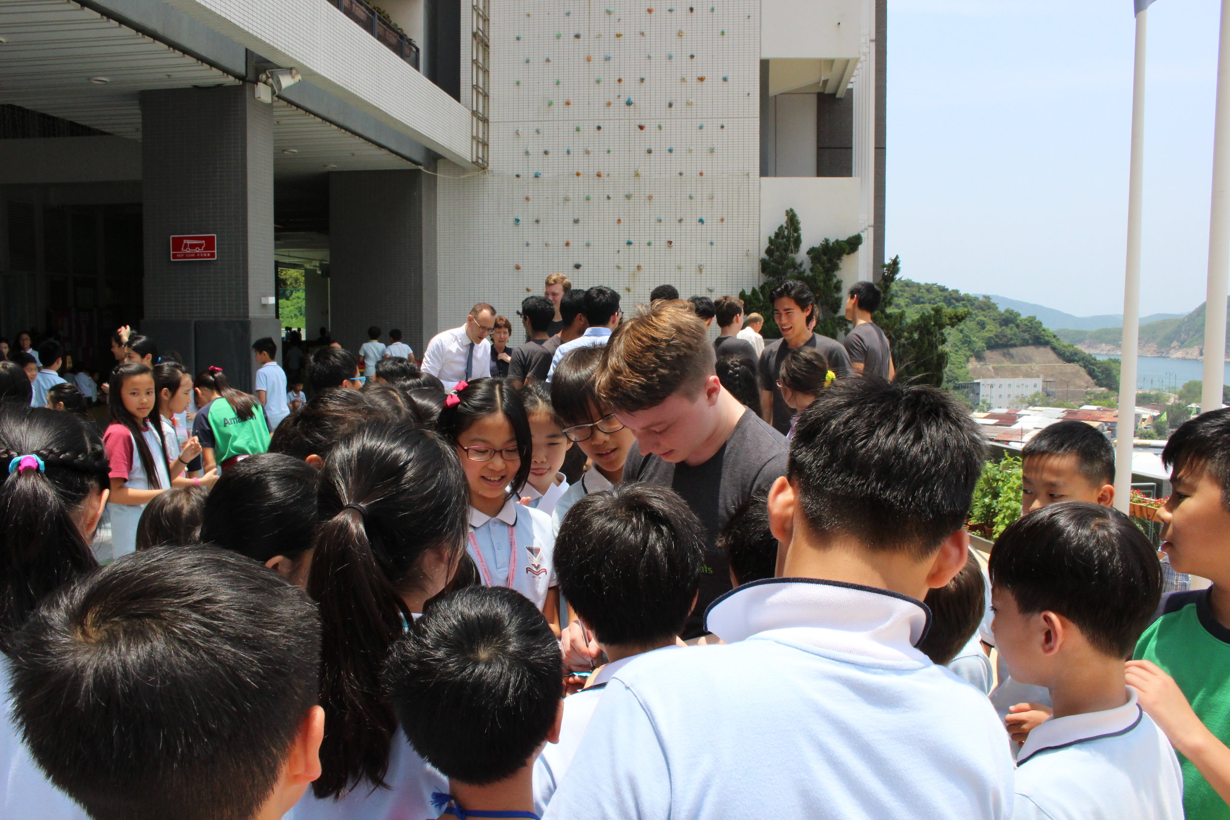 Shaun ('20) signing autographs with students after the concert