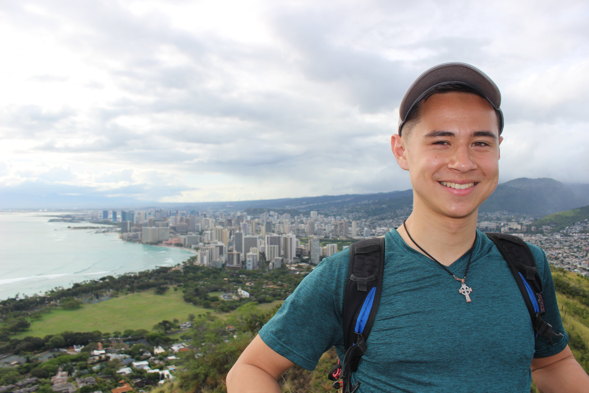 Liam '21 after hiking Diamond Head, with a view of Honolulu
