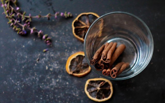Cloves, cinnamon and orange in a glass