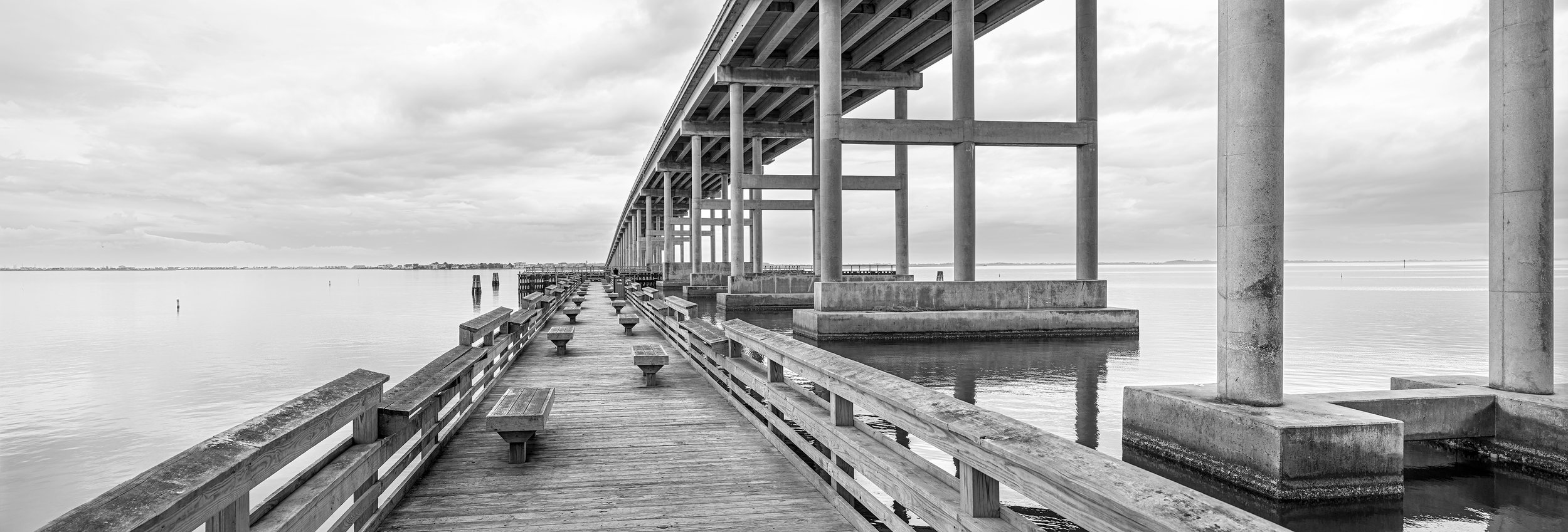 "Washington Baum Bridge. Manteo, NC. Archival Inkjet Print on 100% Cotton Photo Rag, 10"" x 29""  The Washington Baum Bridge is a vital piece of infrastructure that crosses the Roanoke Sound, linking North Carolina's mainland with the Outer Banks and providing easy automobile access to the barrier islands. Underneath, a wooden pier provides an opportunity to fish in the sound."