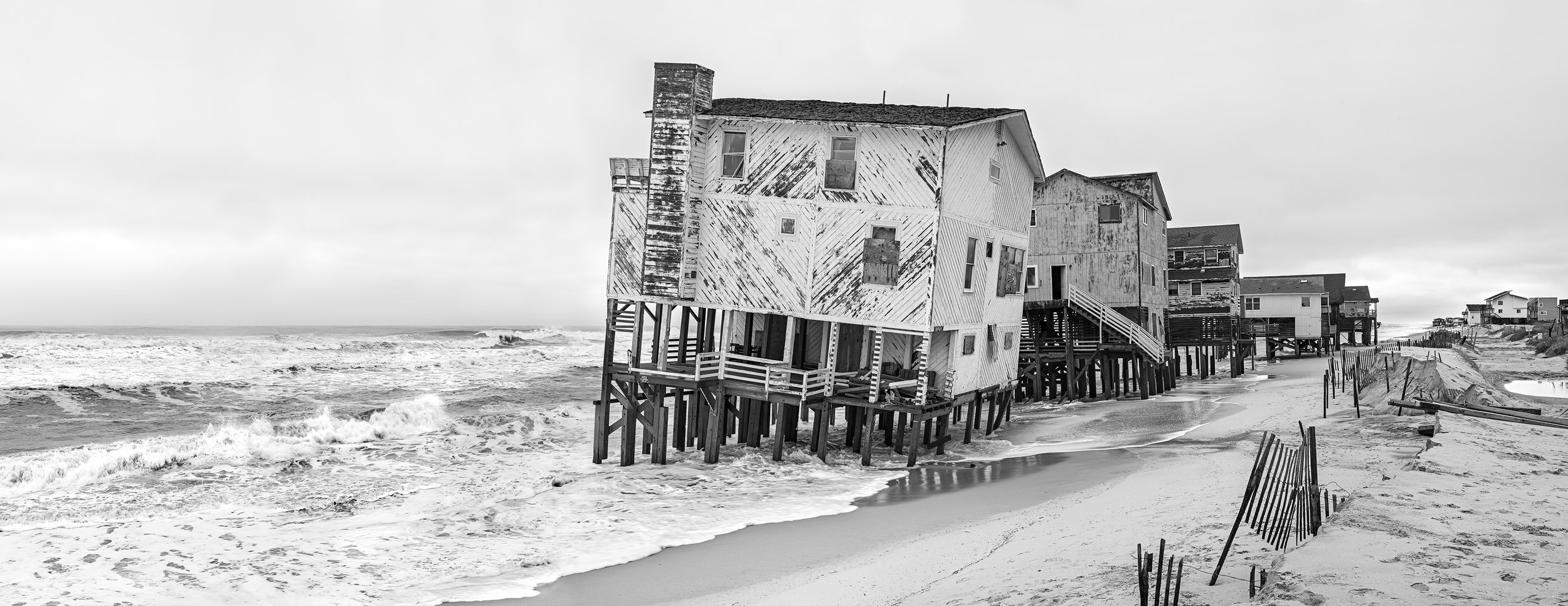 "E Seagull Dr. Nags Head, NC. Archival Inkjet Print on 100% Cotton Photo Rag, 10"" x 25.5""  A strong winter storm hit the town of Nags Head around Veterans Day in 2009, damaging the houses on E Seagull Dr. After the houses were condemned, a lengthy legal battle ensued, questioning the limits of private property rights and the ability of the town to protect the public beaches. After 5 years in court and $1.5 million settlement, the houses were finally removed."