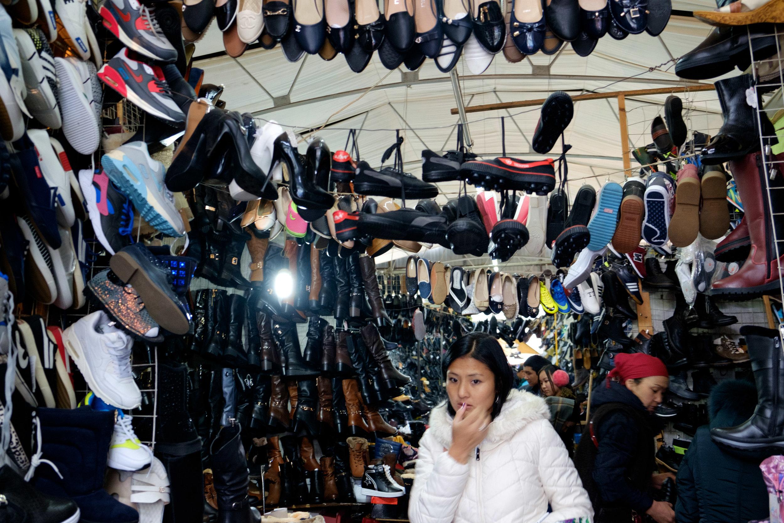Une femme inquiète de ne pas trouver la paire de souliers parfaite dans ce bazaar.