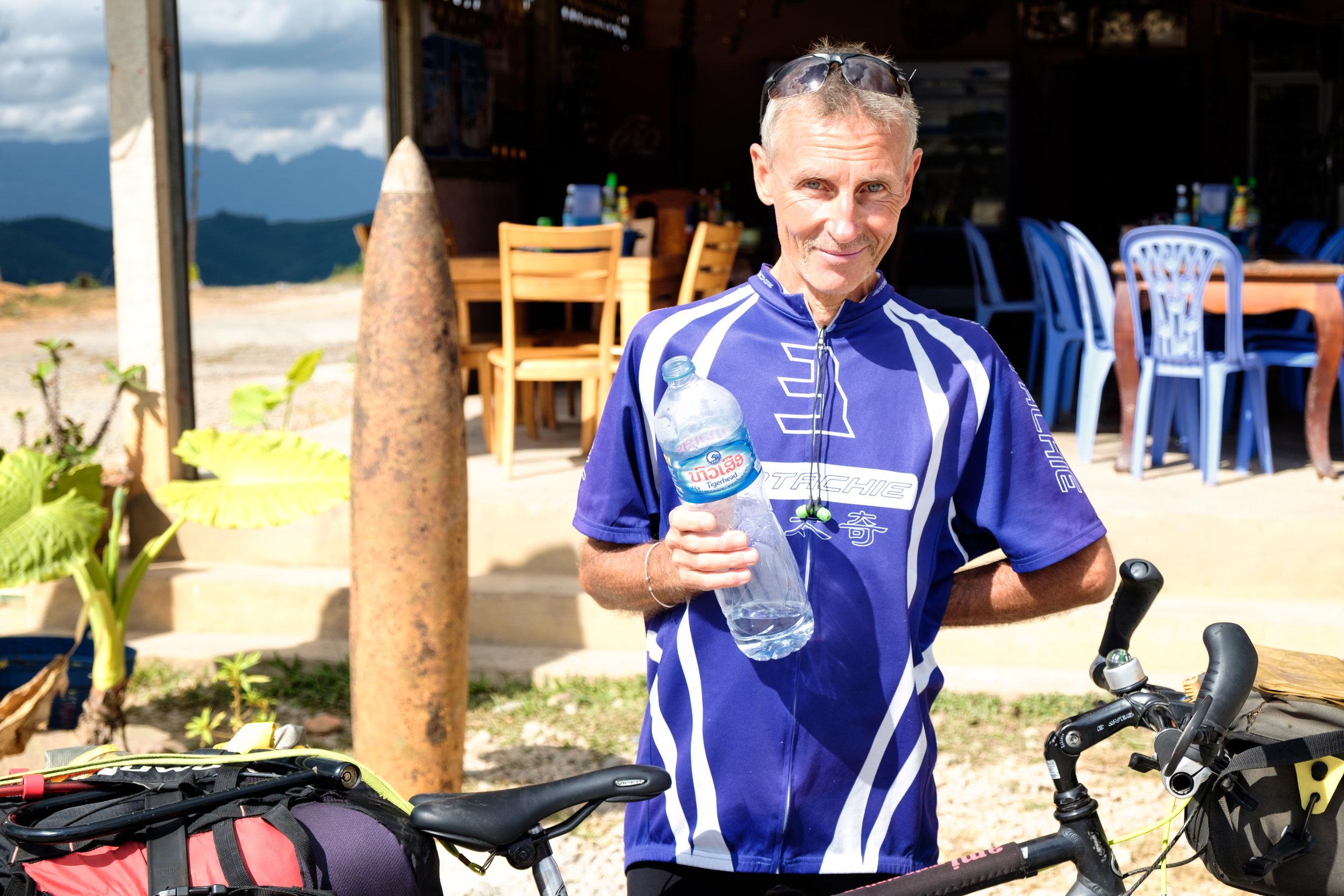 Tim, un cycliste britannique rencontré plus loin dans les montagnes. On aperçoit un vieil obus à l'arrière servant de décoration à un restaurant.