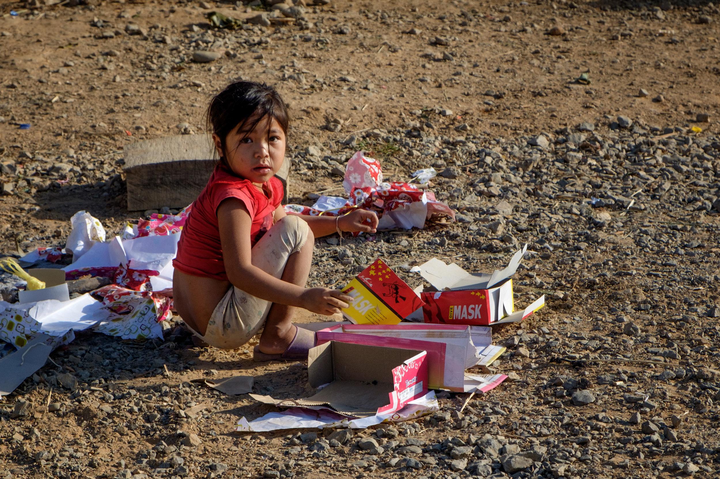 Une petite fille qui n'a que du carton comme jouet.