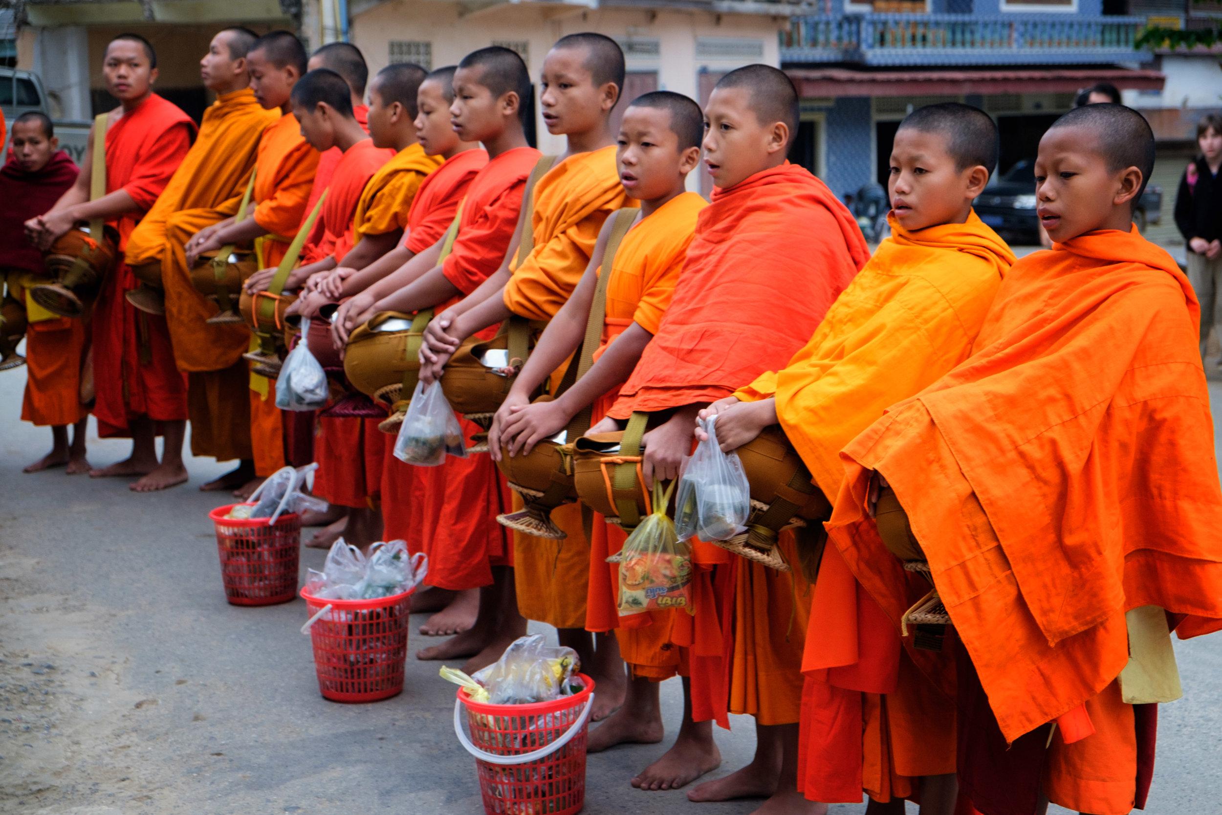 À chaque matin, les moines laotiens passent pour se faire donner de la nourriture.