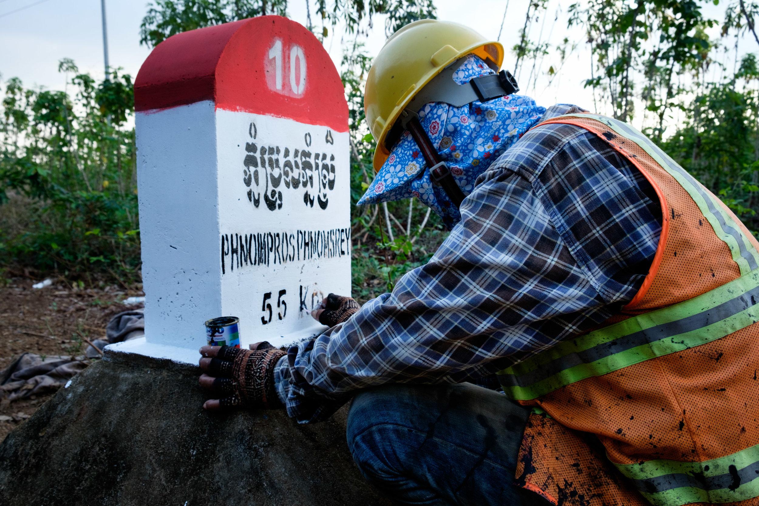 Un travailleur met à jour les inscriptions sur les bornes en bordure de route. Son outil : un Q-Tips !