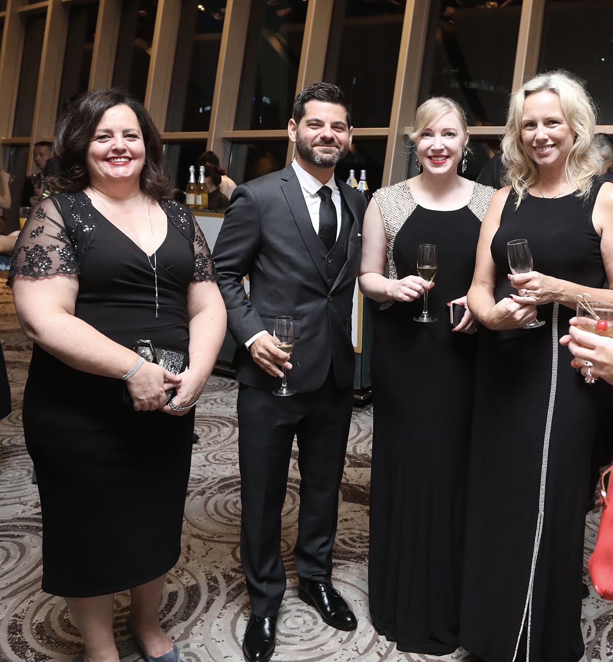 En habit de gala, entouré de Brigitte et d'Hélène, la présidente de la CanCham.