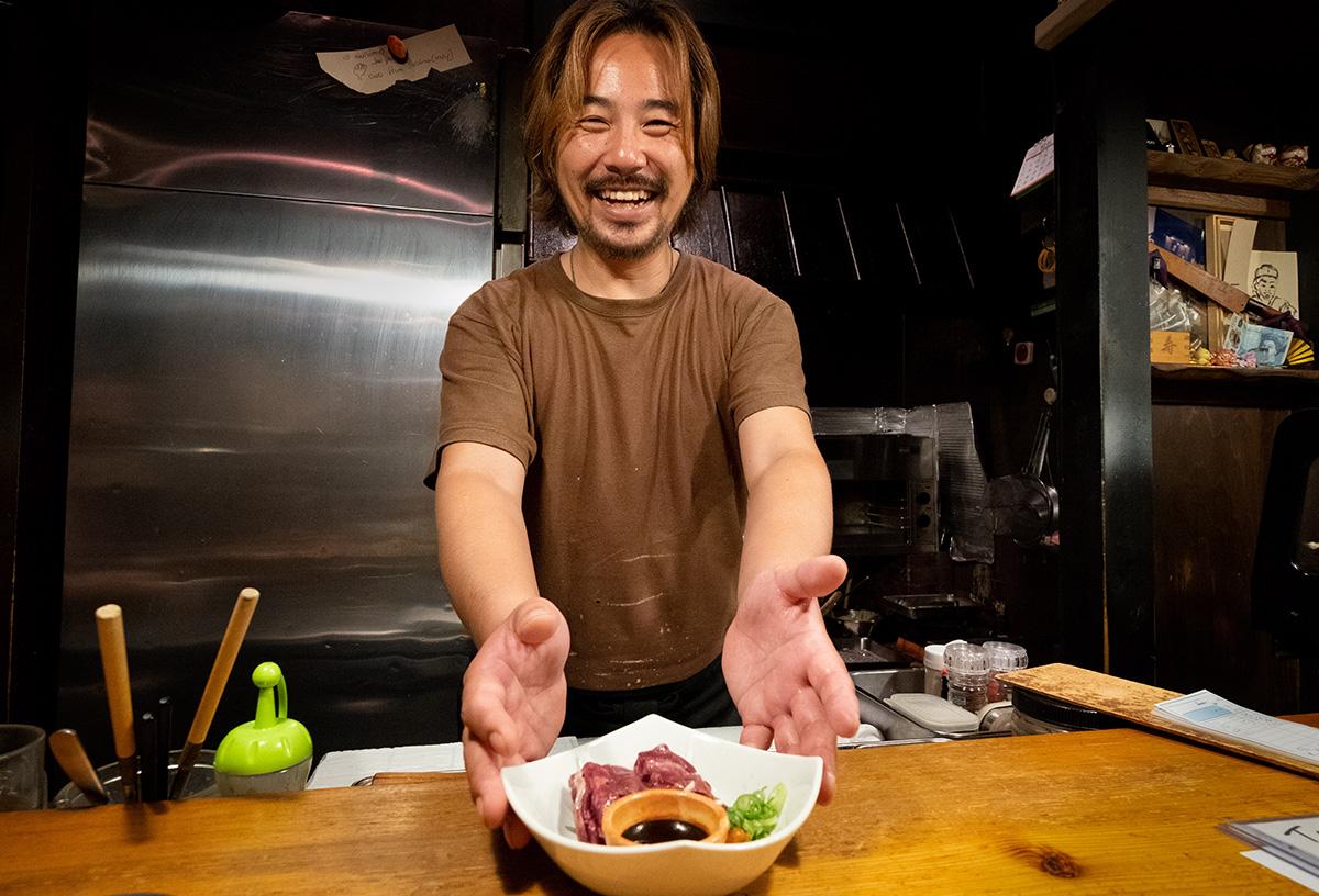 Taku, me montrant avec fierté la langue de cheval crue que je viens de commander dans son restaurant de Kobé. Bien qu'un peu musculeux, c'était quand même assez bon !
