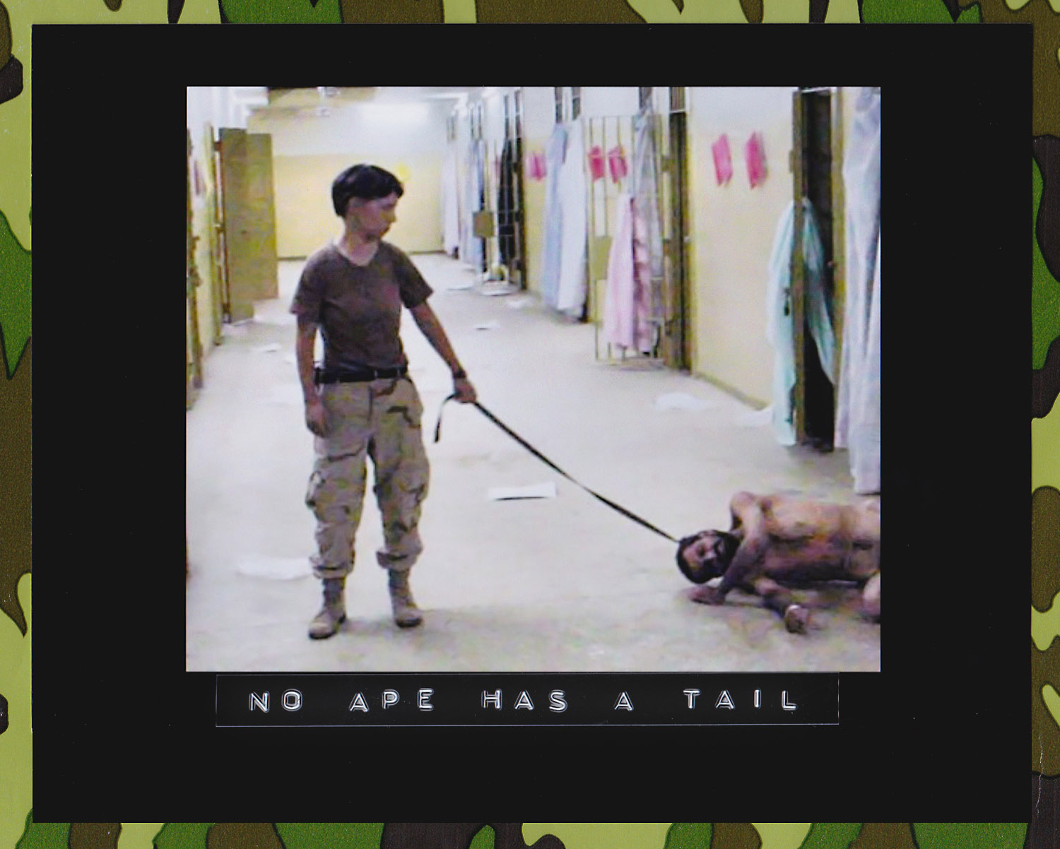 """U.S. Army photo from Abu Ghraib prison in Iraq showing Pvt. Lynndie England holding a leash attached to a prisoner collapsed on the floor, known to the guards as """"Gus."""" (Source: U.S. Army. Department of Defense)"""