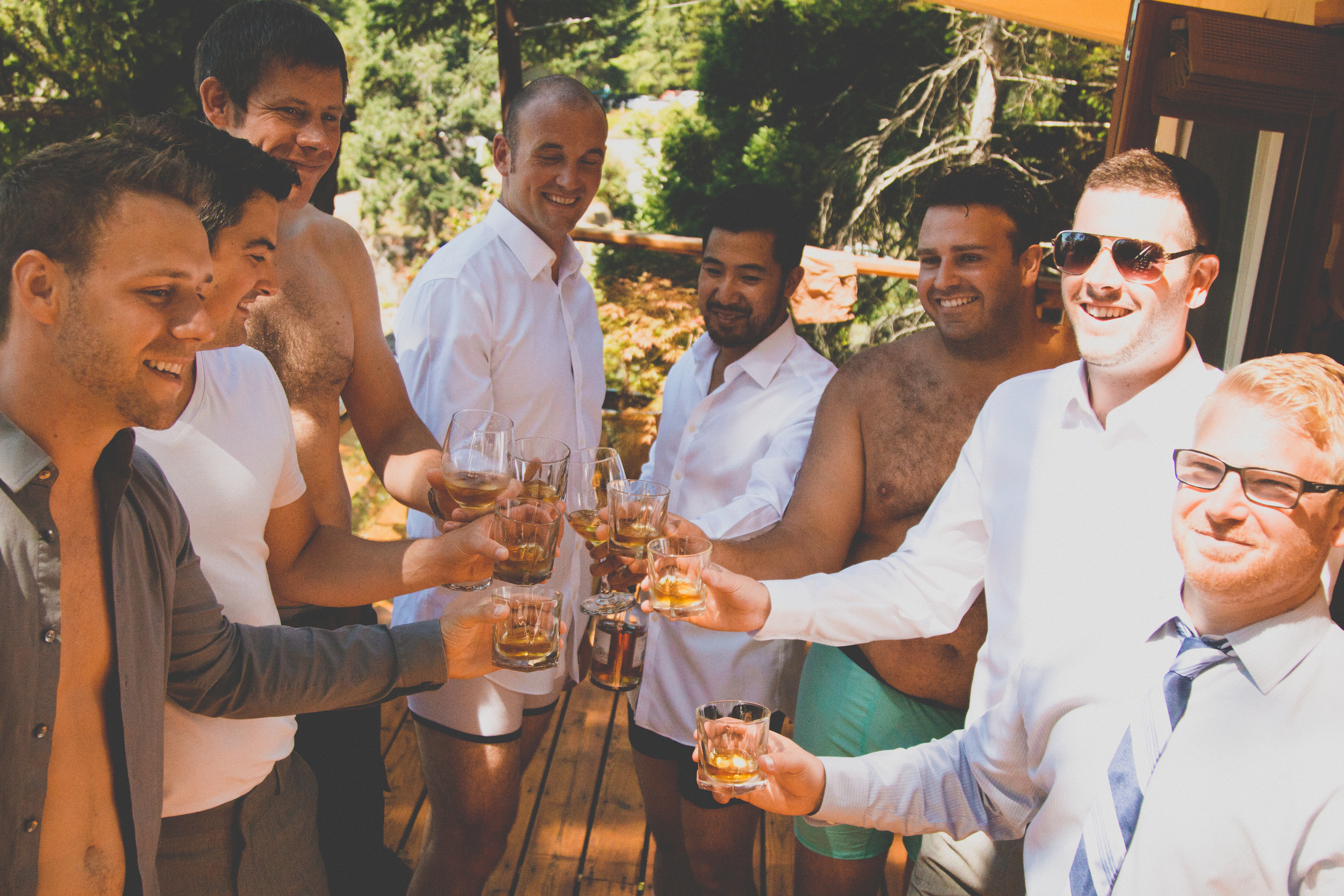 Groomsmen drinking scotch while putting on suits  at Rockwater Secret cove elopement and wedding spot
