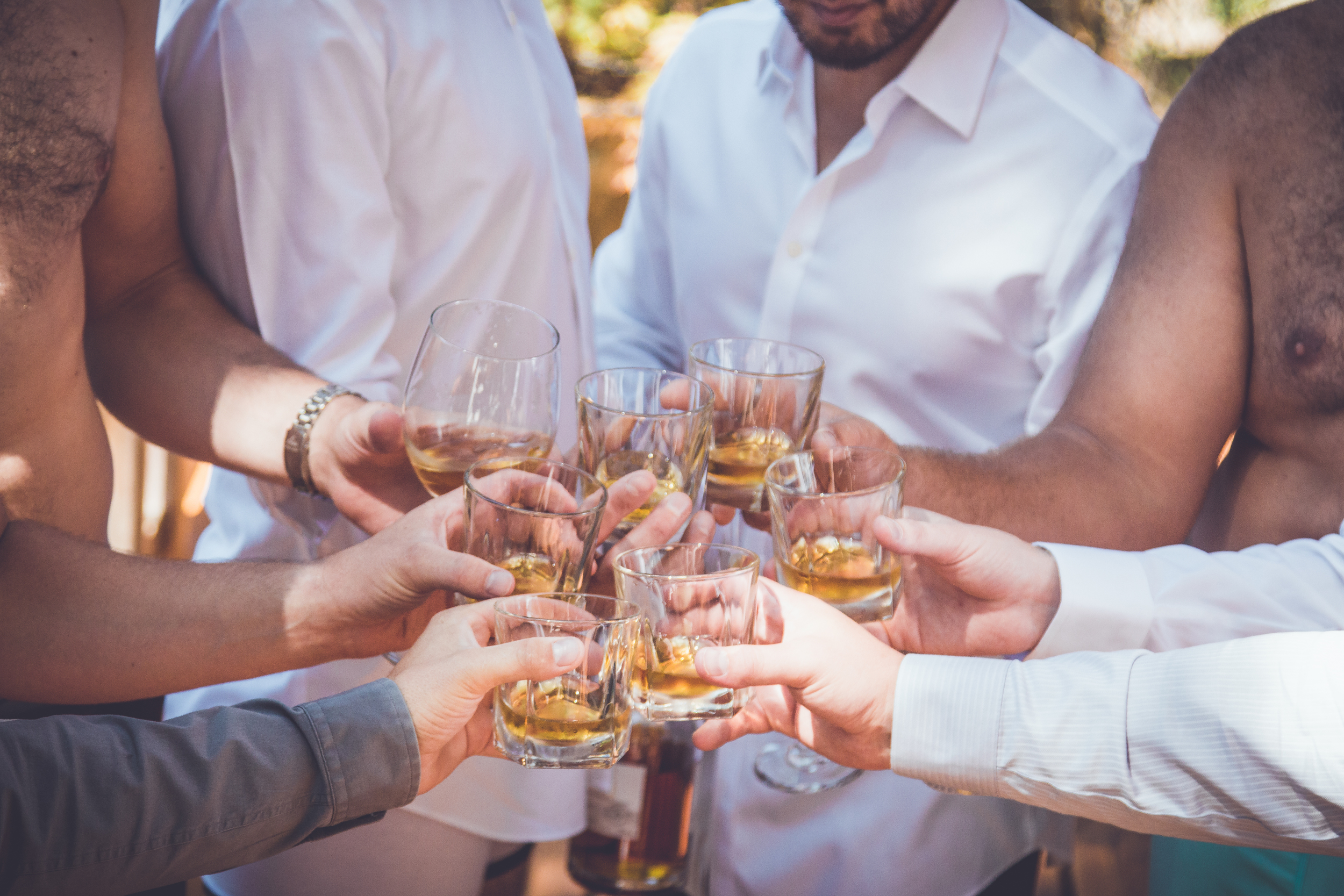 Groomsmen drinking scotch while getting ready  at Rockwater Secret cove elopement and wedding spot