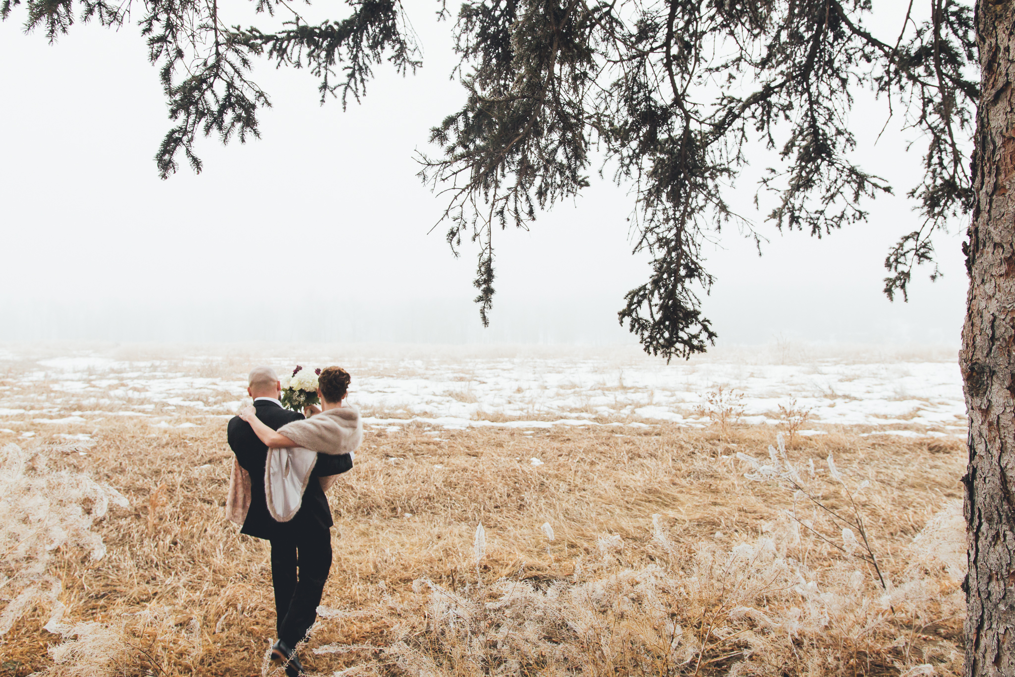 Groom carrying bride through foggy field near Bow Valley Ranche Restaurant