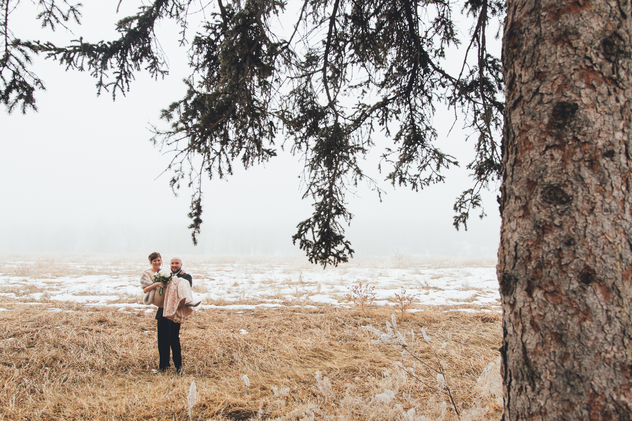 Groom holding bride in foggy field at Bow Valley Ranche wedding