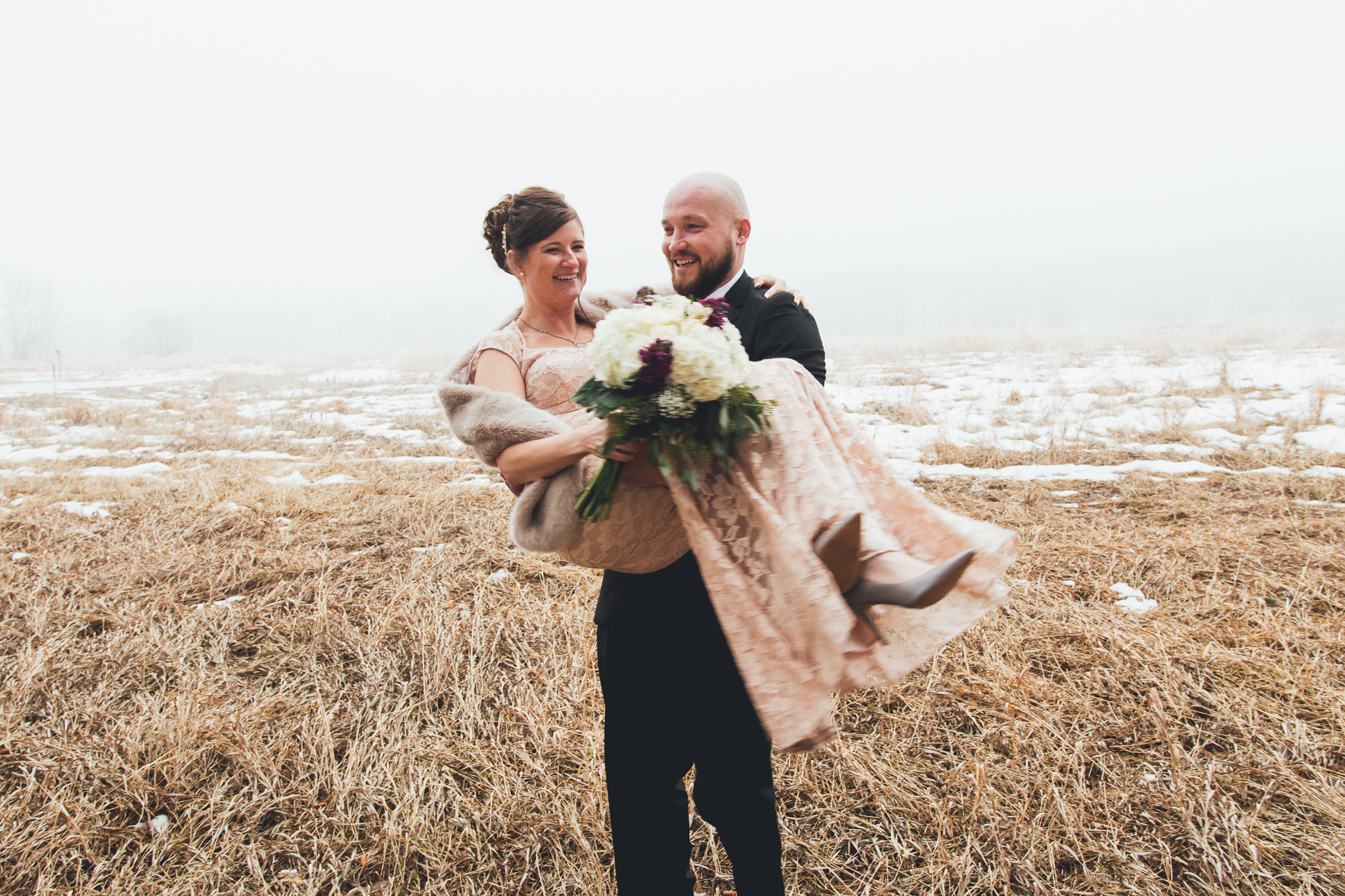 Close up of groom holding bride in foggy field outside of Bow Valley Ranche wedding