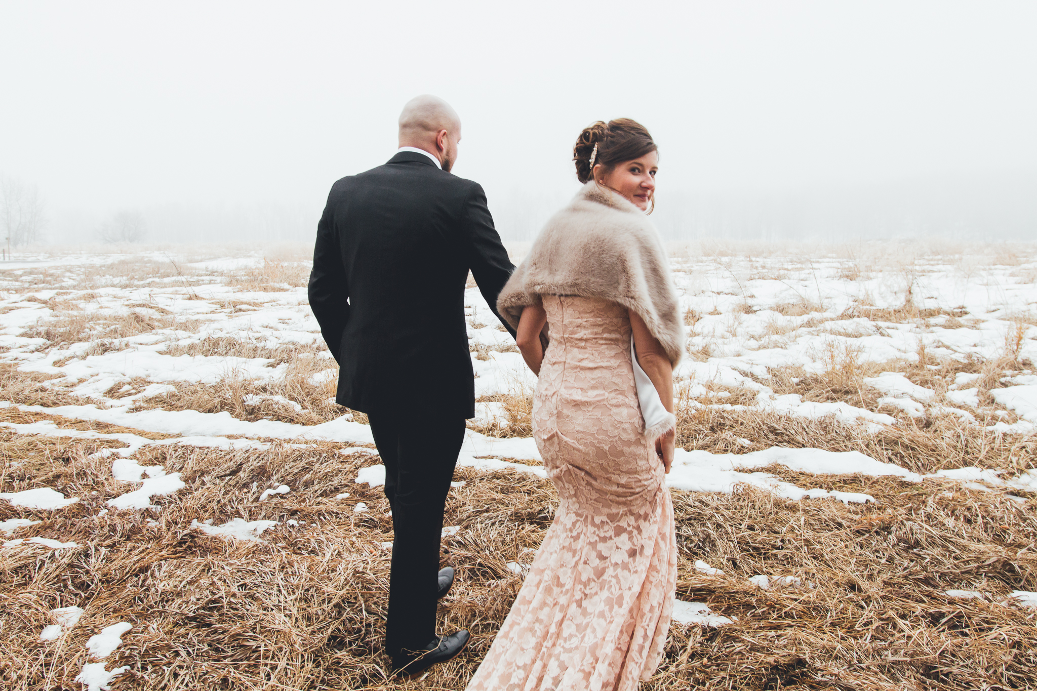 Bride and groom walking into foggy field after wedding at Bow Valley Ranche