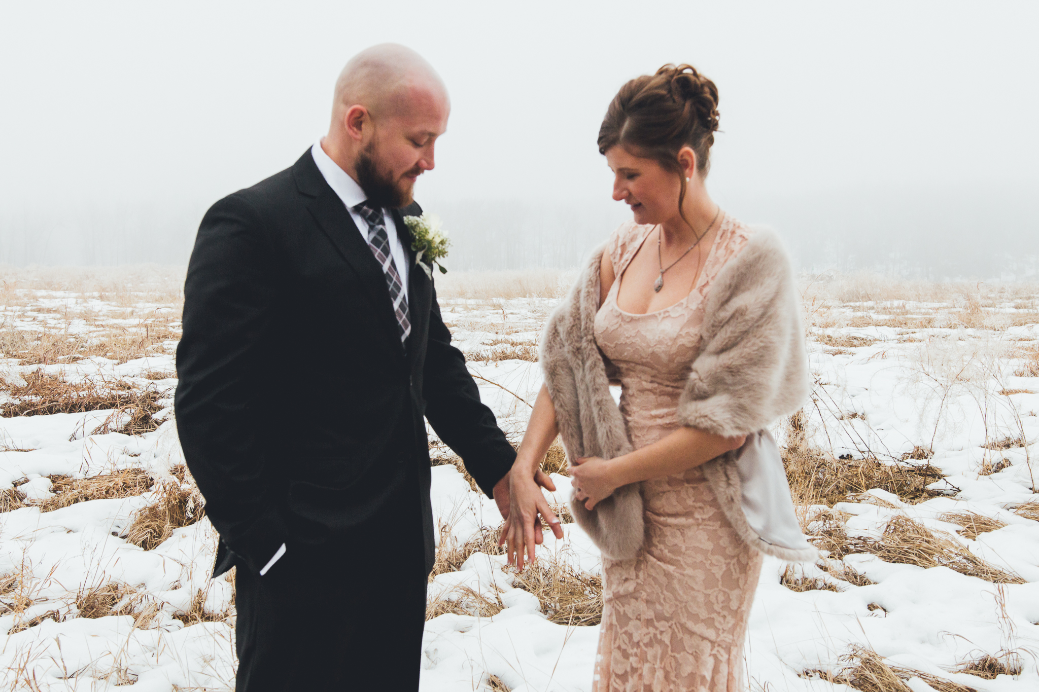 Bride and groom holding hands in snowy foggy field after wedding at Bow Valley Ranche