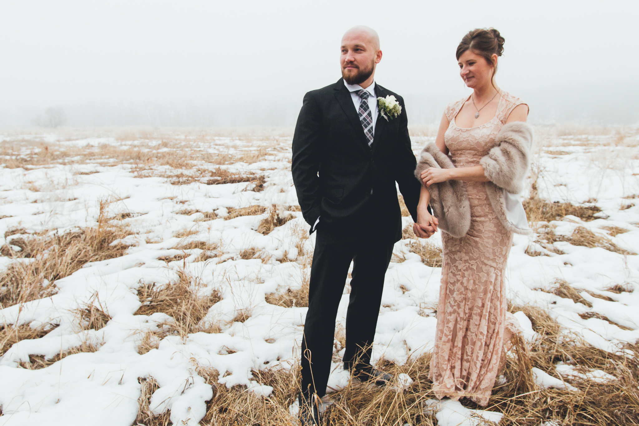 Bride and groom holding hands in snowy foggy field before wedding at Bow Valley Ranche