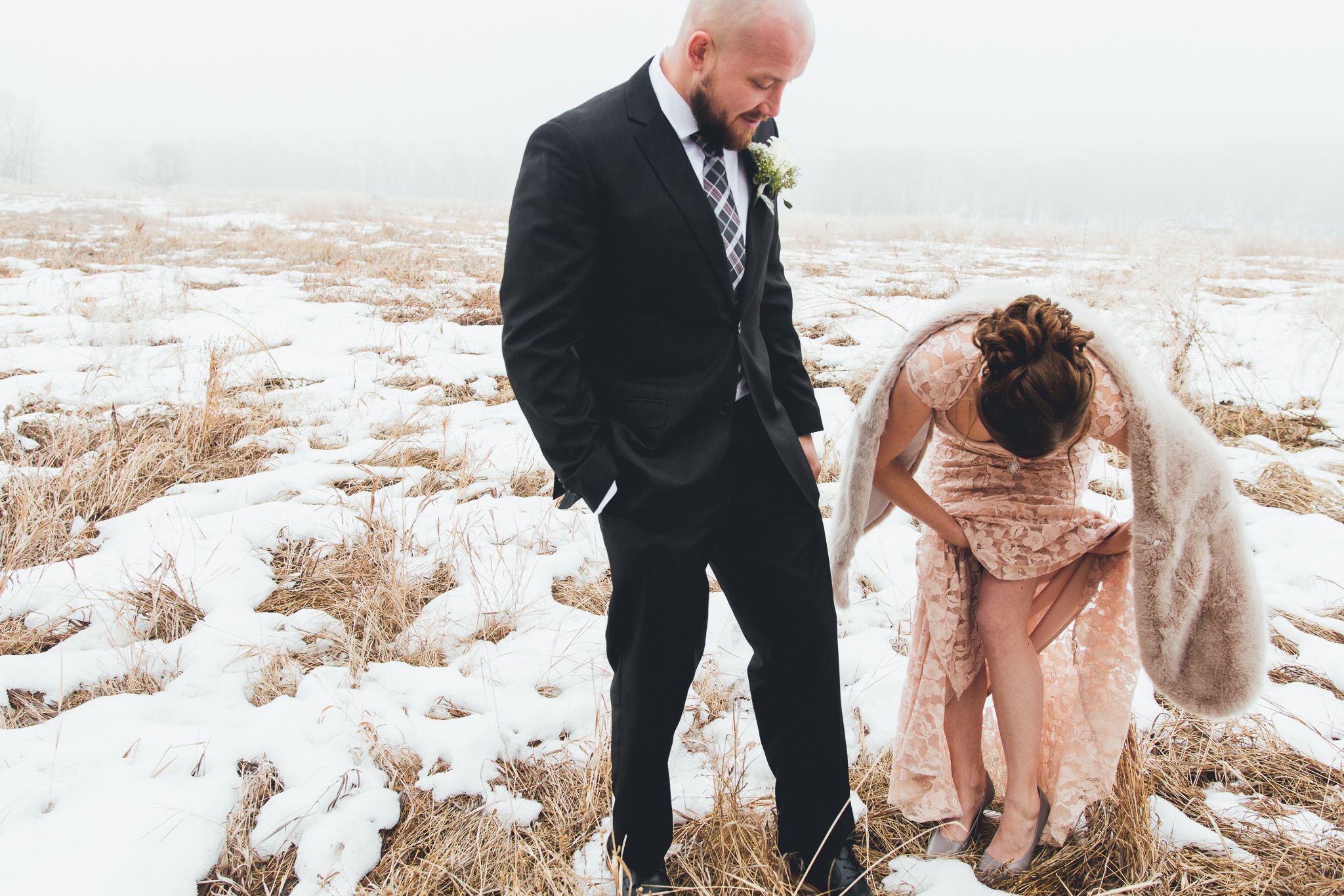 Bride fixing her dress while groom watches in foggy field after wedding at Bow Valley Ranche