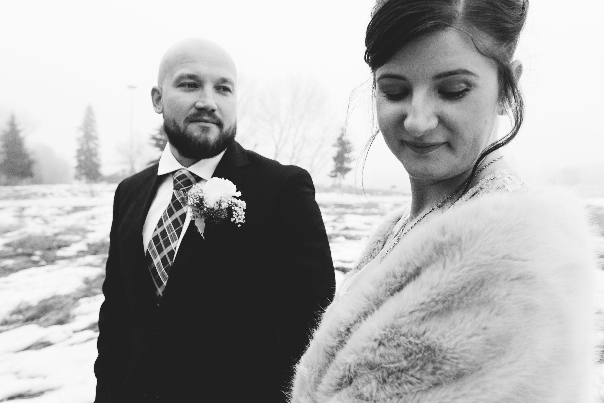 Black and white portrait of groom looking at bride wearing fur shawl in field outside of Bow Valley Ranche
