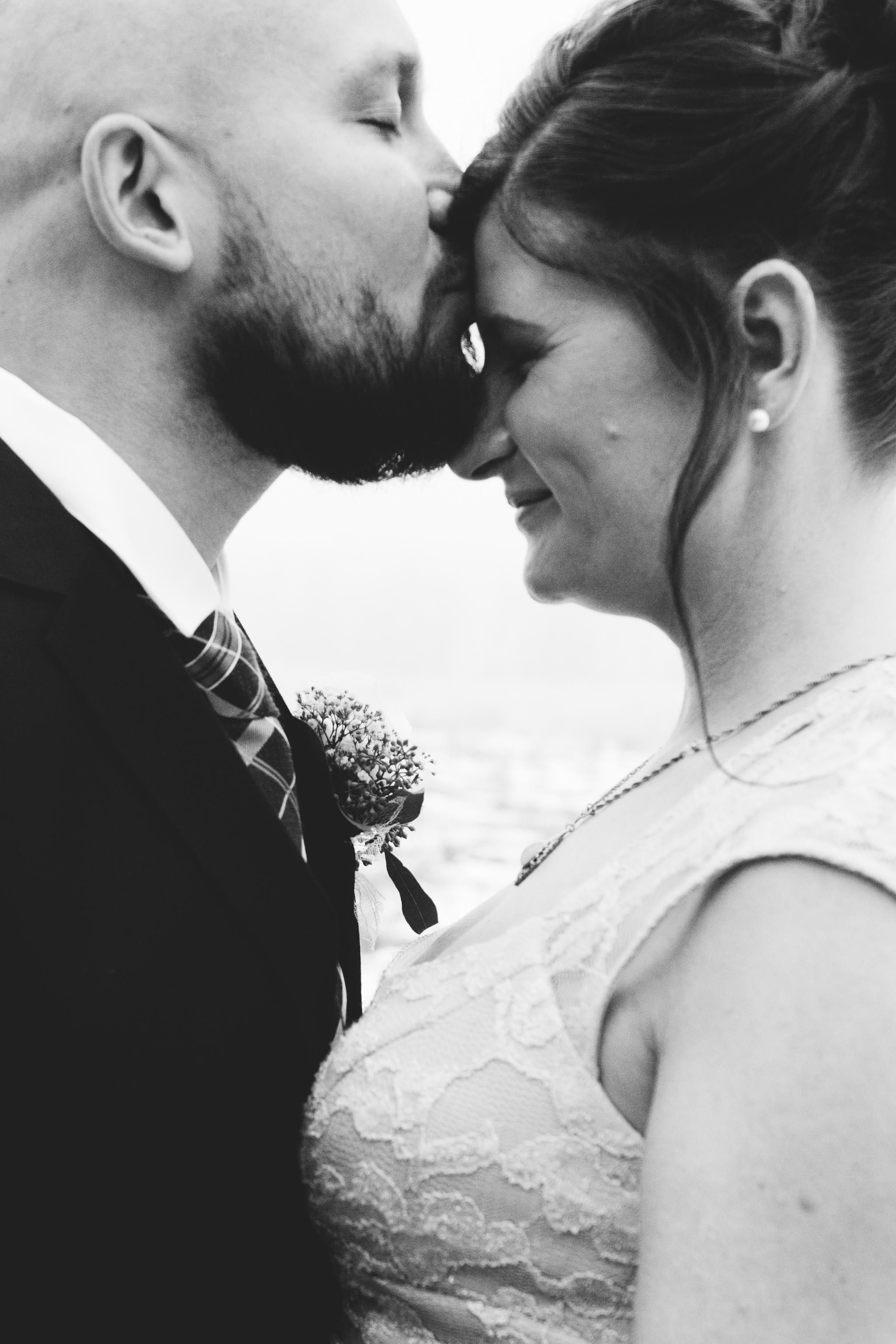 Black and white portrait of groom kissing bride on forehead in foggy Fish Creek park wedding