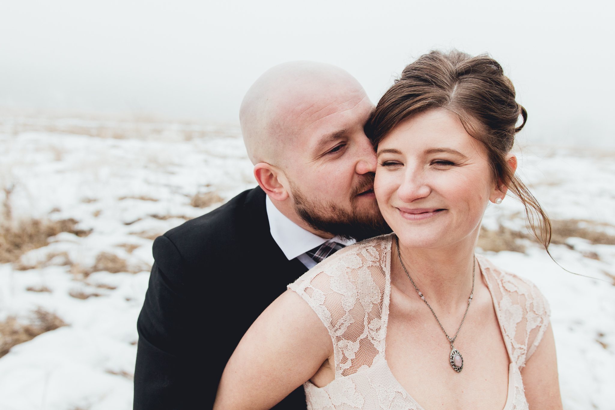 Groom kissing bride on cheek from behind at intimate winter wedding at Bow Valley Ranche