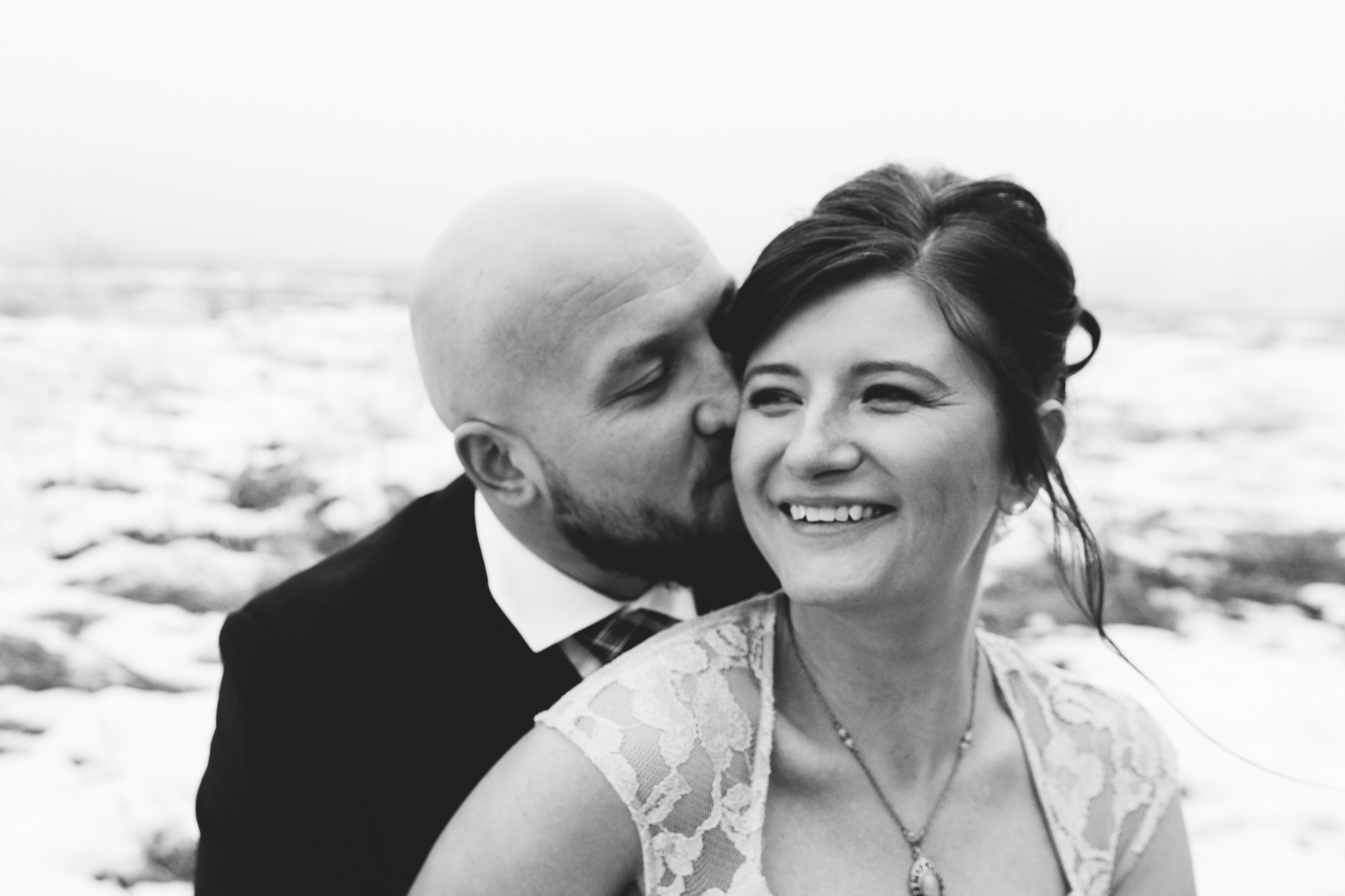 Black and white portrait of groom kissing bride on cheek at intimate winter wedding at Bow Valley Ranche