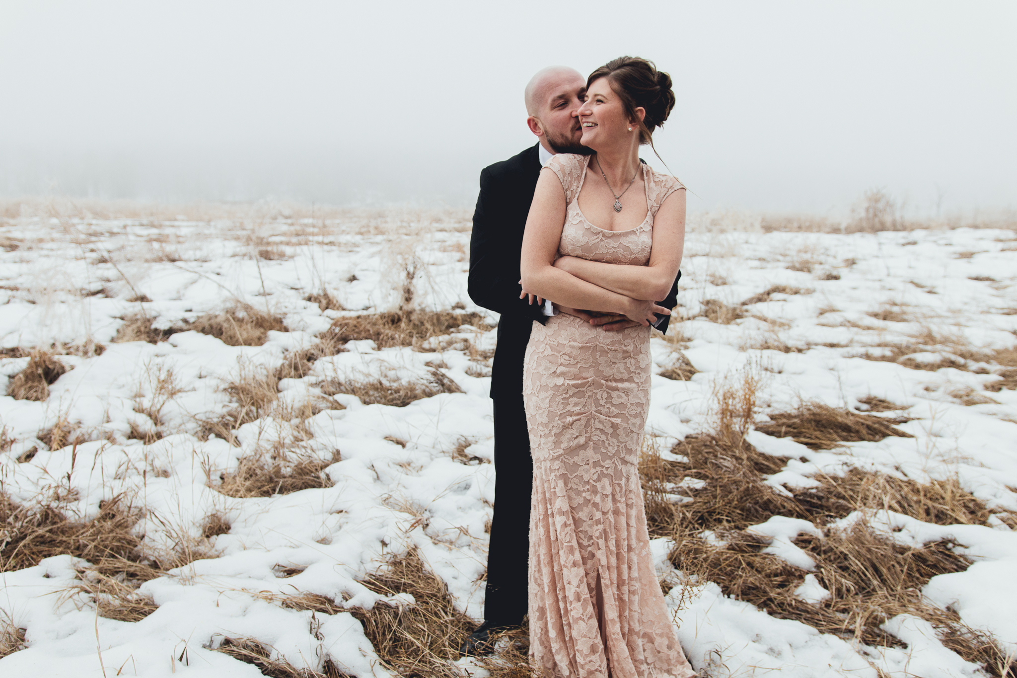 Bride and groom cuddling in snowy field in Fish Creek Park before intimate winter wedding