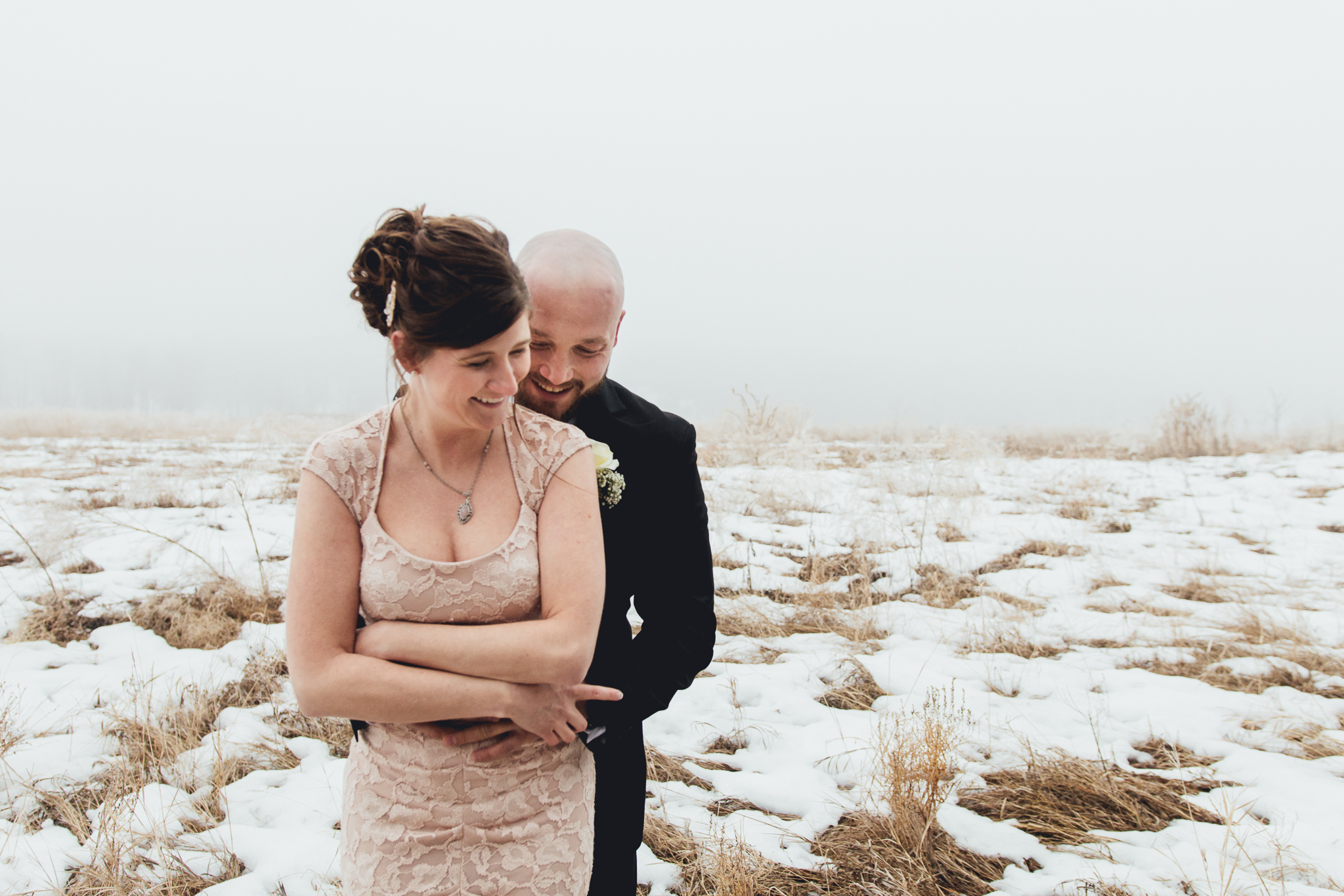 Groom holding bride from behind in foggy field during intimate winter wedding at Bow Valley Ranche
