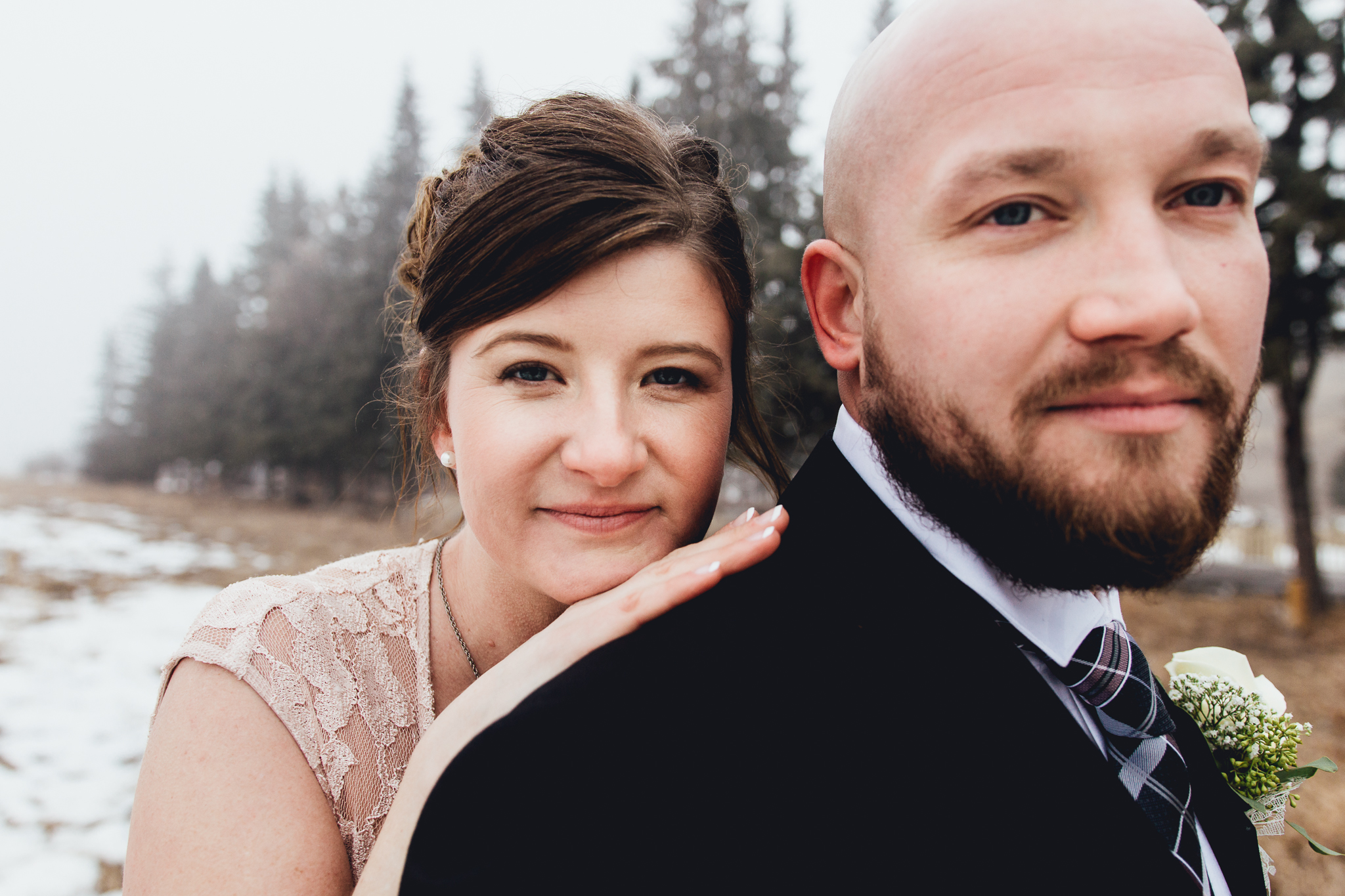 Close up of bride and groom cuddling in foggy field during intimate winter wedding Calgary