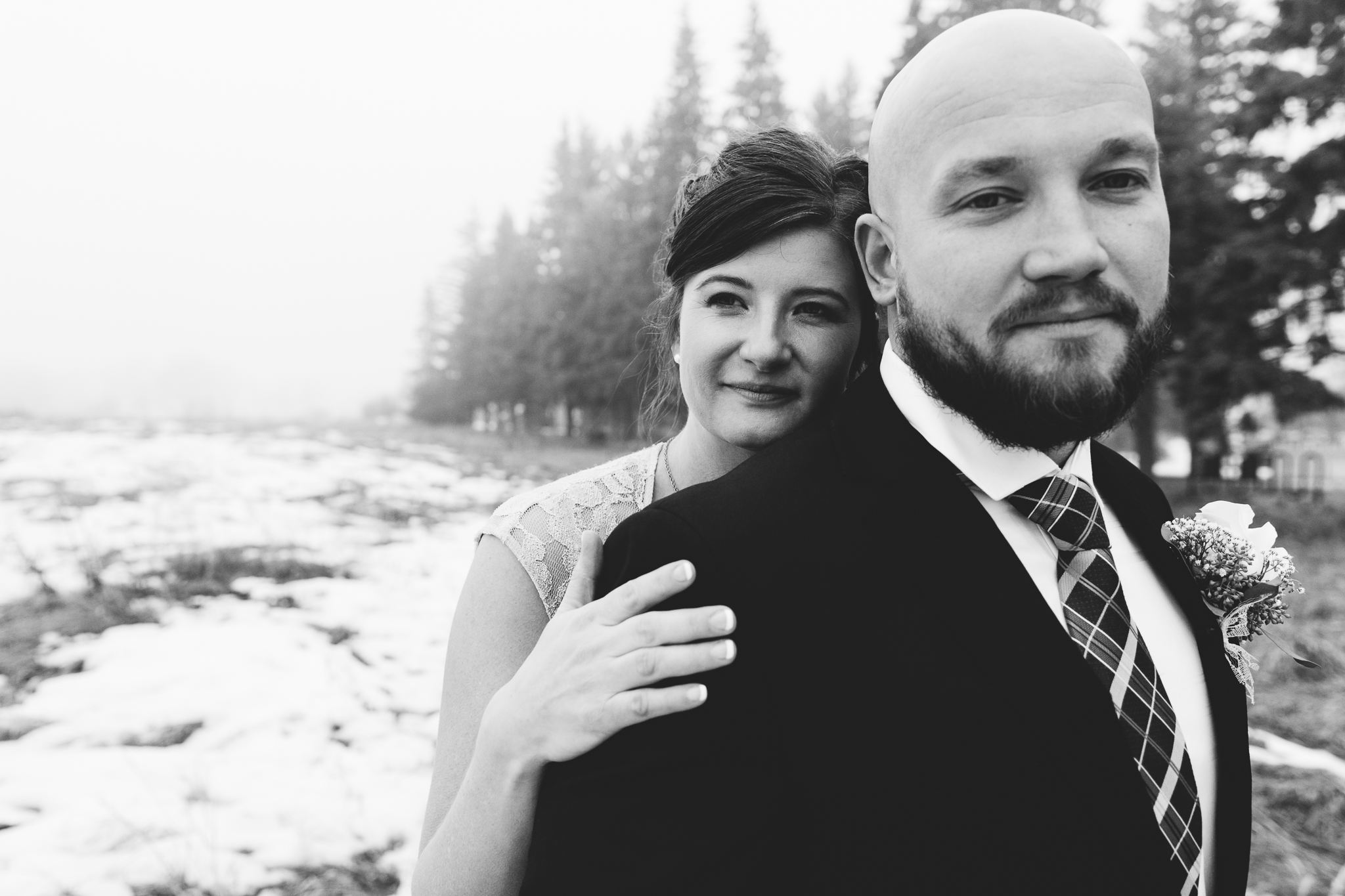 Black and white close up of bride and groom snuggling before intimate winter wedding at Bow Valley Ranche