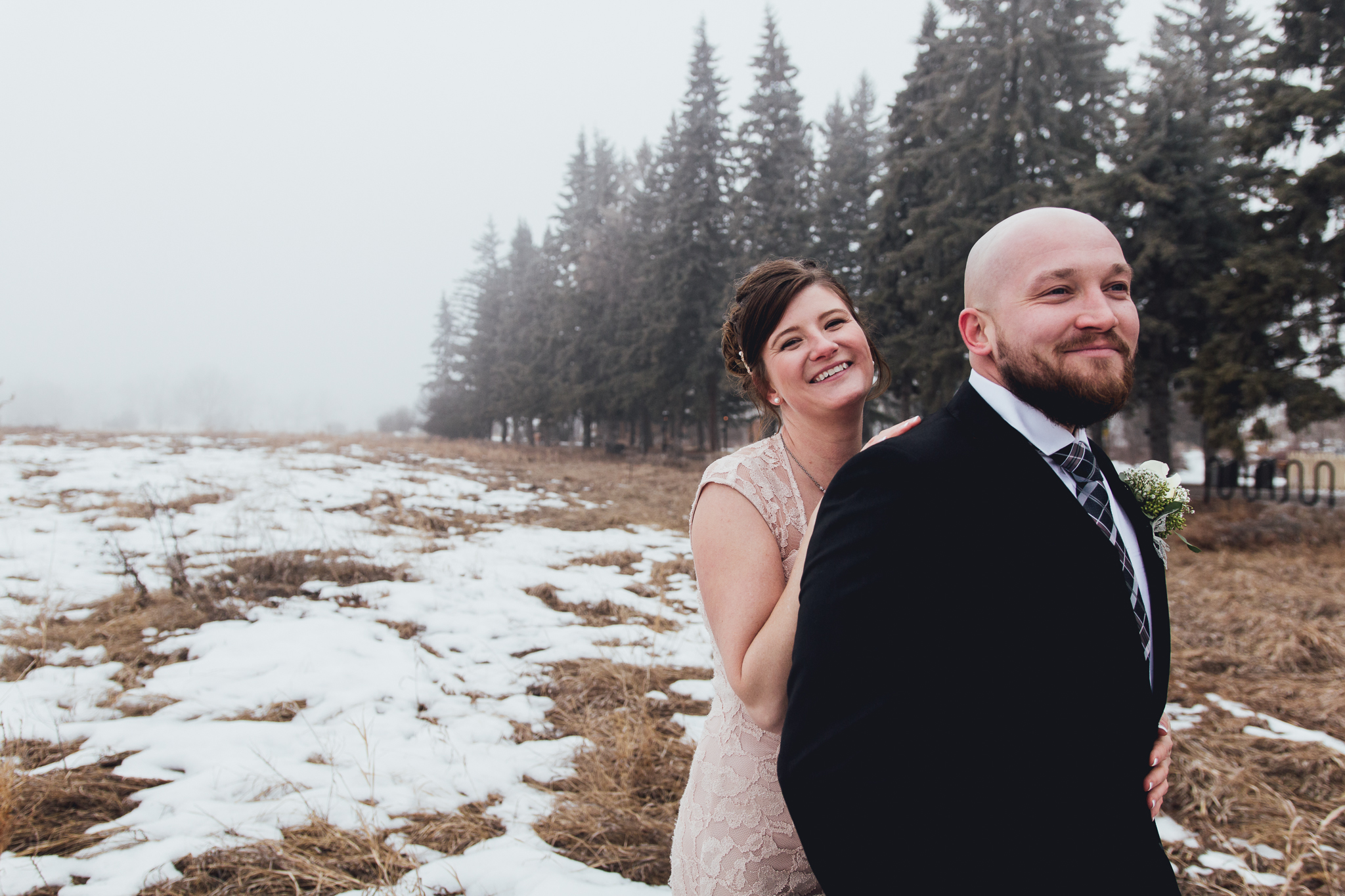 Bride and groom laughing in foggy field during intimate winter wedding at Bow Valley Ranche