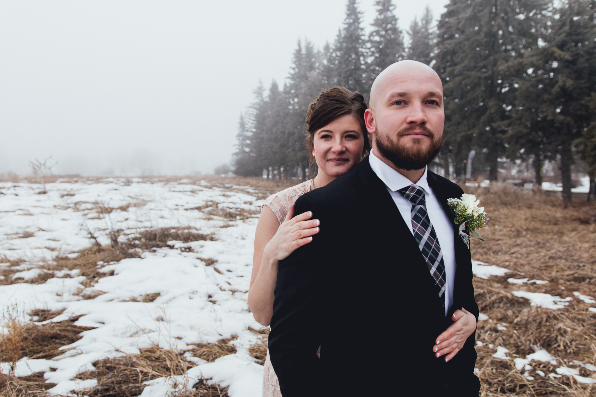 Bride holding groom from behind with foggy field and row of fir trees near Bow Valley Ranche