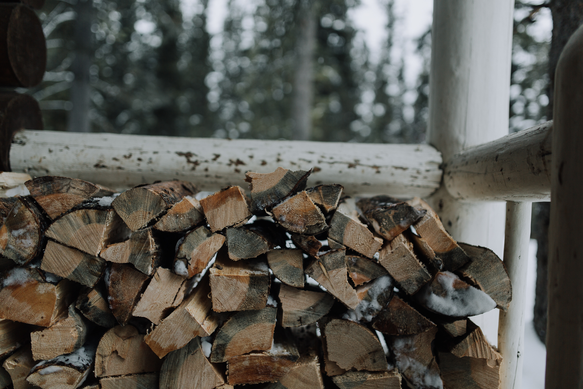 Pile of wood on cabin deck at Storm Mountain Lodge wedding.