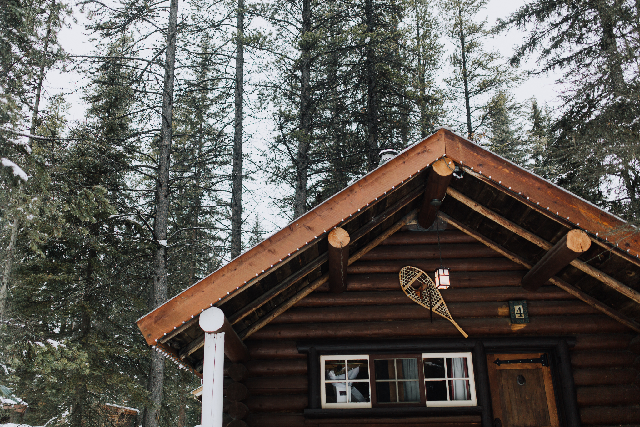 Cabin surrounded by trees with snowshoe above door at Storm Mountain Lodge winter wedding.