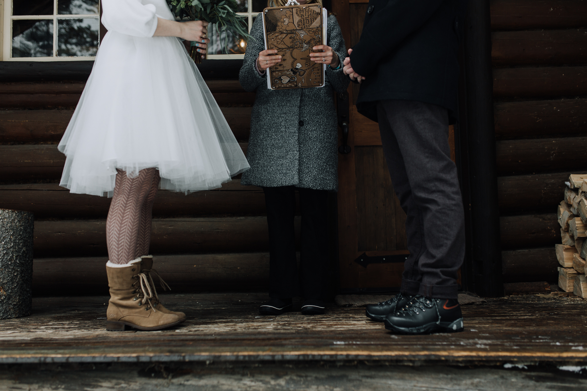 Bride and groom wearing snow boots on log cabin porch during winter wedding at Storm Mountain Lodge in Banff