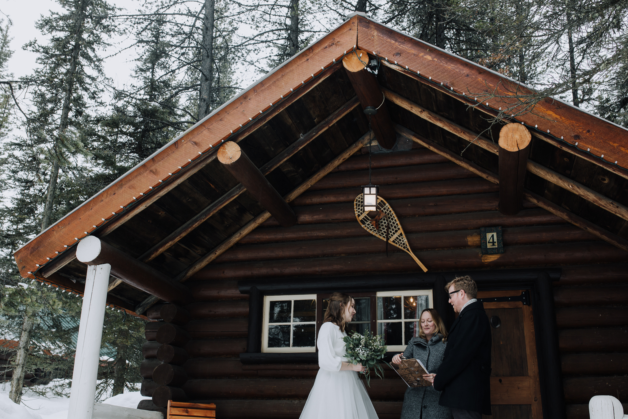 Bride and groom eloping on cute log cabin porch at Storm Mountain Lodge winter wedding
