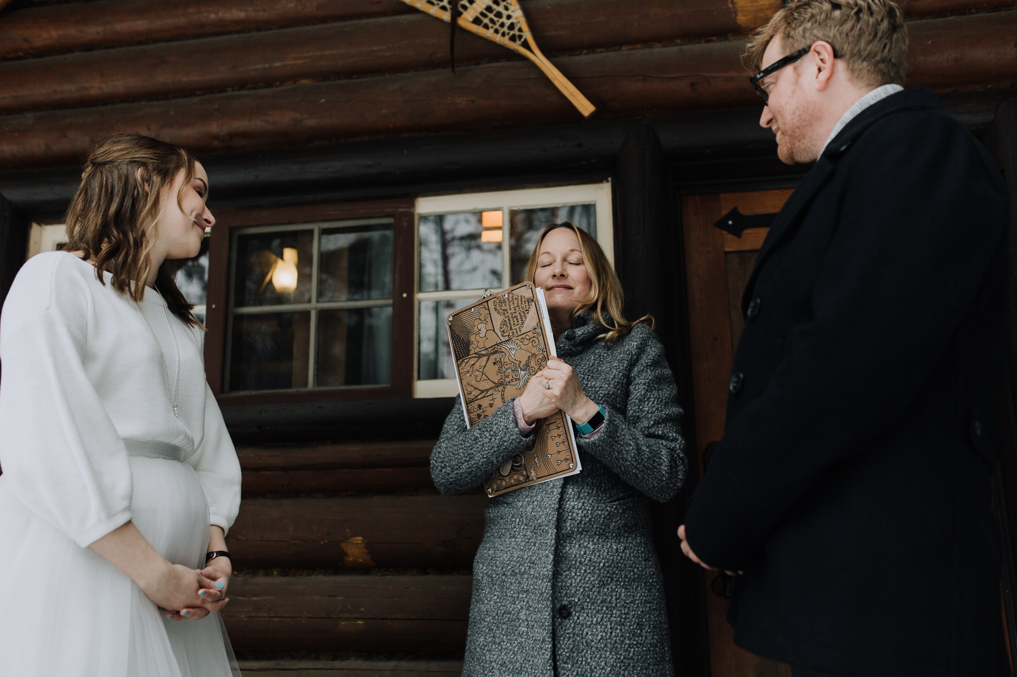 Ring ceremony on cute log cabin porch at Storm Mountain Lodge winter wedding