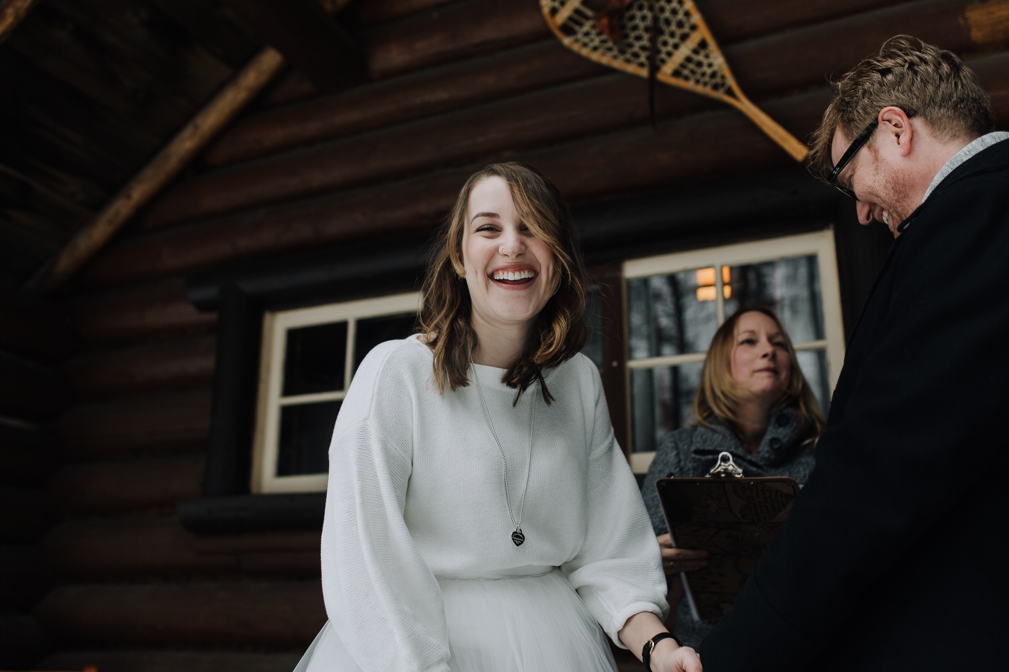 Bride laughing during elopement ceremony at Storm Mountain Lodge winter wedding